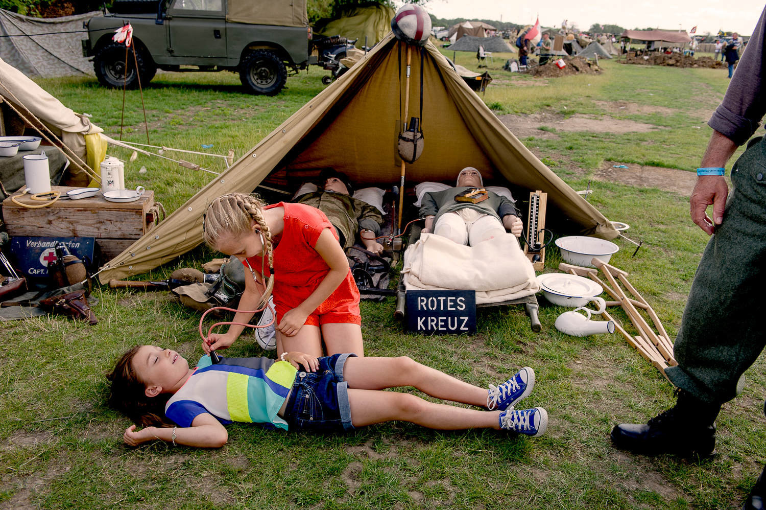 Girls playing in front of a display of a German field hospital tent. Re-enactment event in Essex