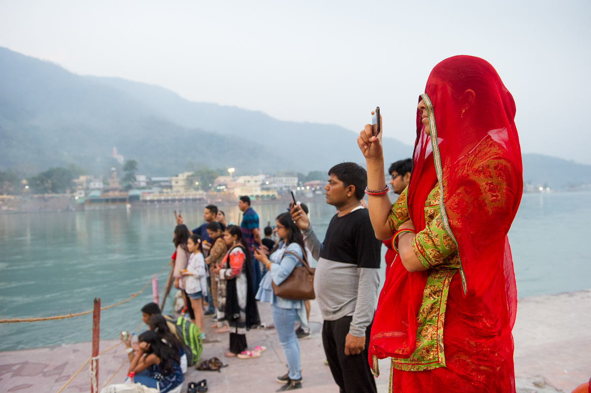 young woman filming The Artti ceremony in Rishikesh, 2019