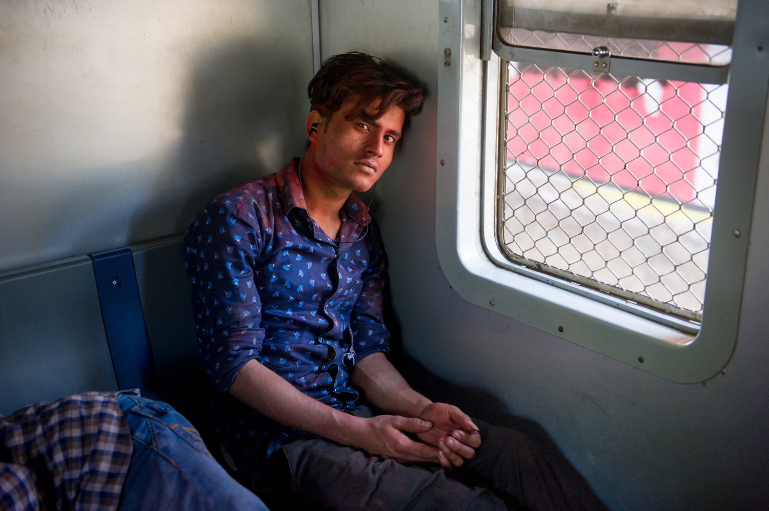 Young man travelling on a local train following The annual celebration of Holi, Mumbai, 2019