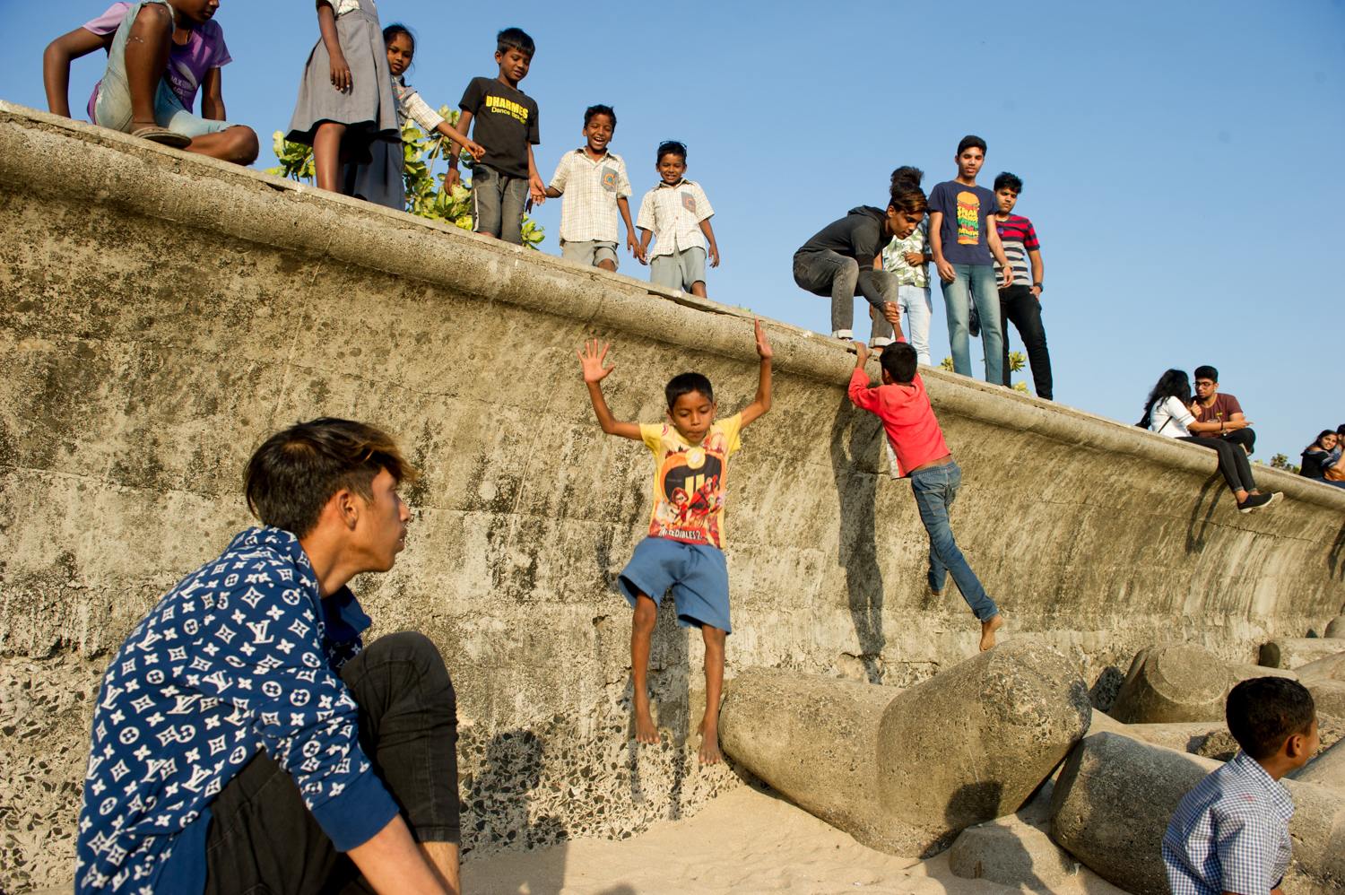 Children jumping off Boardwalk onto the Beach, Mumbai 2019