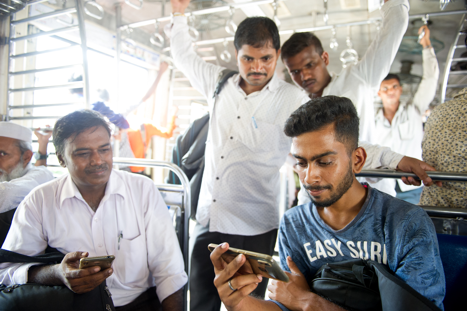 Watching cricket on a local train, Mumbai, 2019