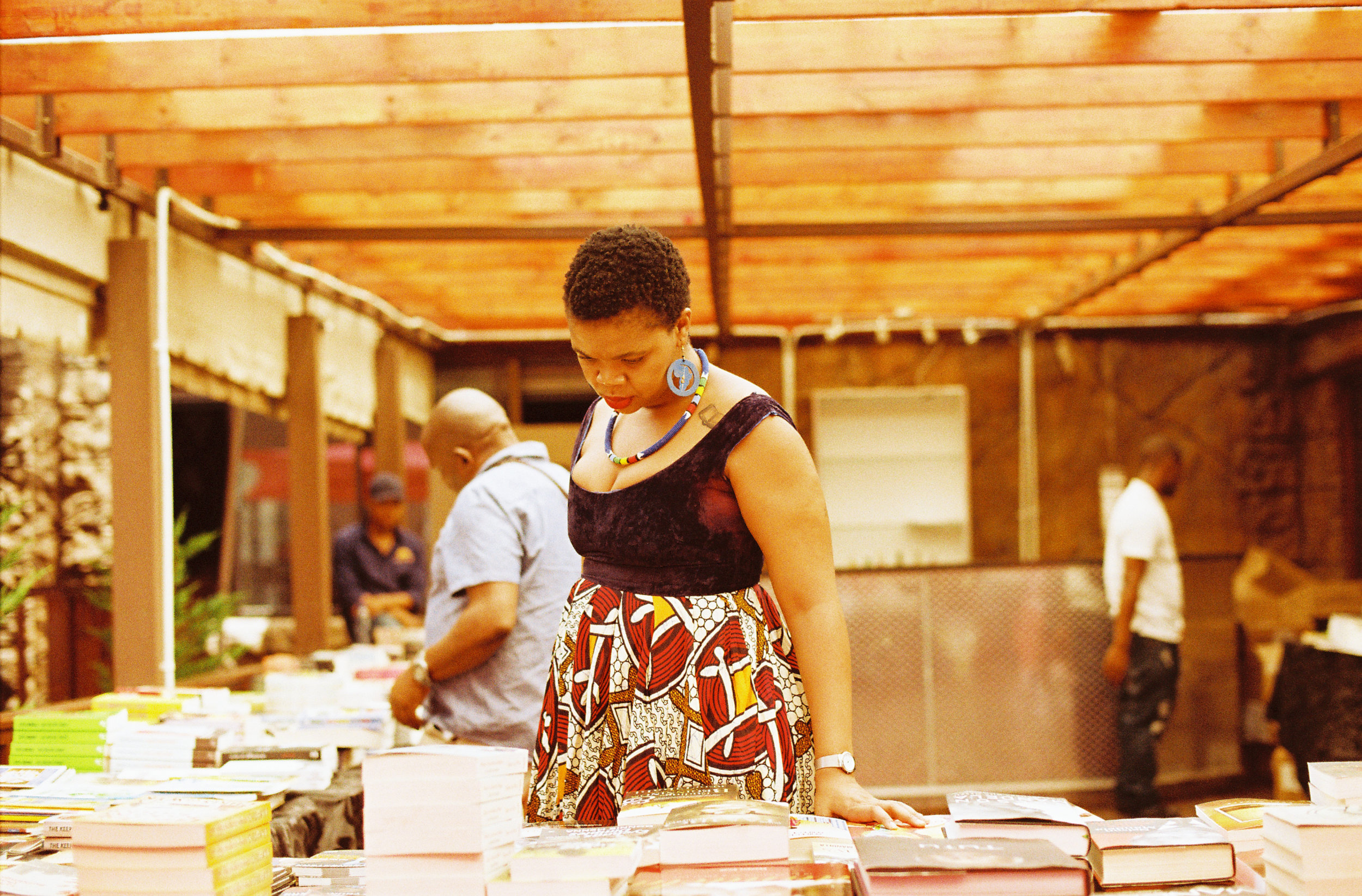Captured at Abantu Book Festival browsing book titles, Malebo Sephodi. Photo credit: Lidudumalingani