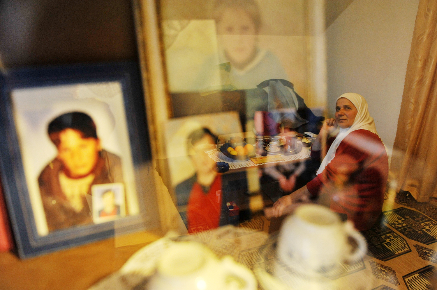 Hatidza Mehmedovic, a Bosnian Muslim woman survivor of the 1995 Srebrenica massacre,is looking at photos of her husband and her two sons who were killed during 1995 Srebrenica massacre.