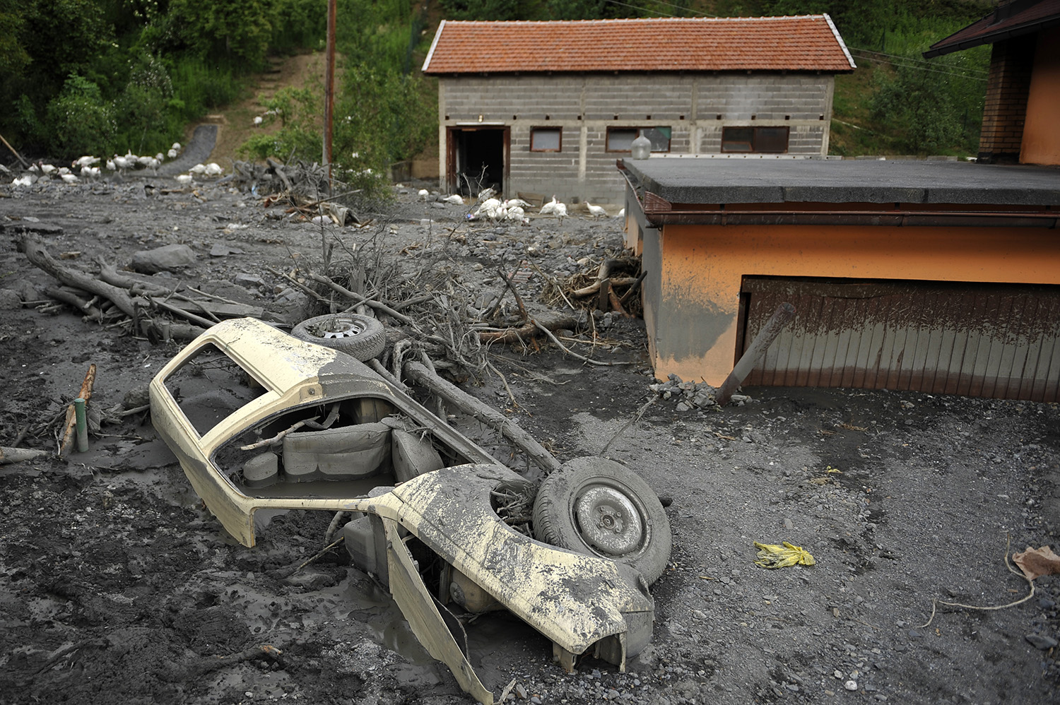 Car buried in mud and rubble after a landslide at the village of Topcic Polje , near Zenica.