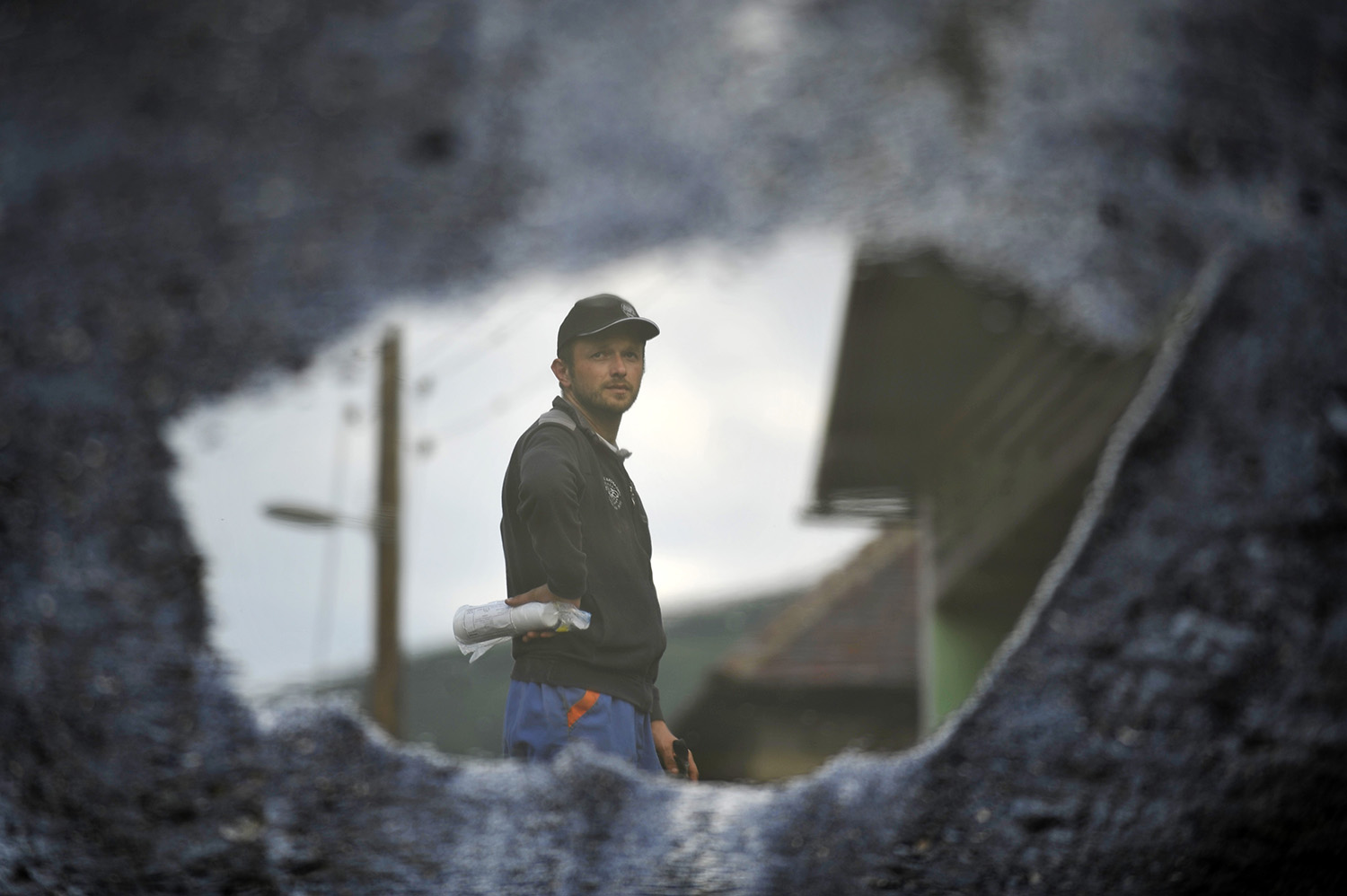Reflection in a puddle of a man standing next to a house wich is buried in mud and rubble after a landslide at the village of Topcic Polje , near Zenica.