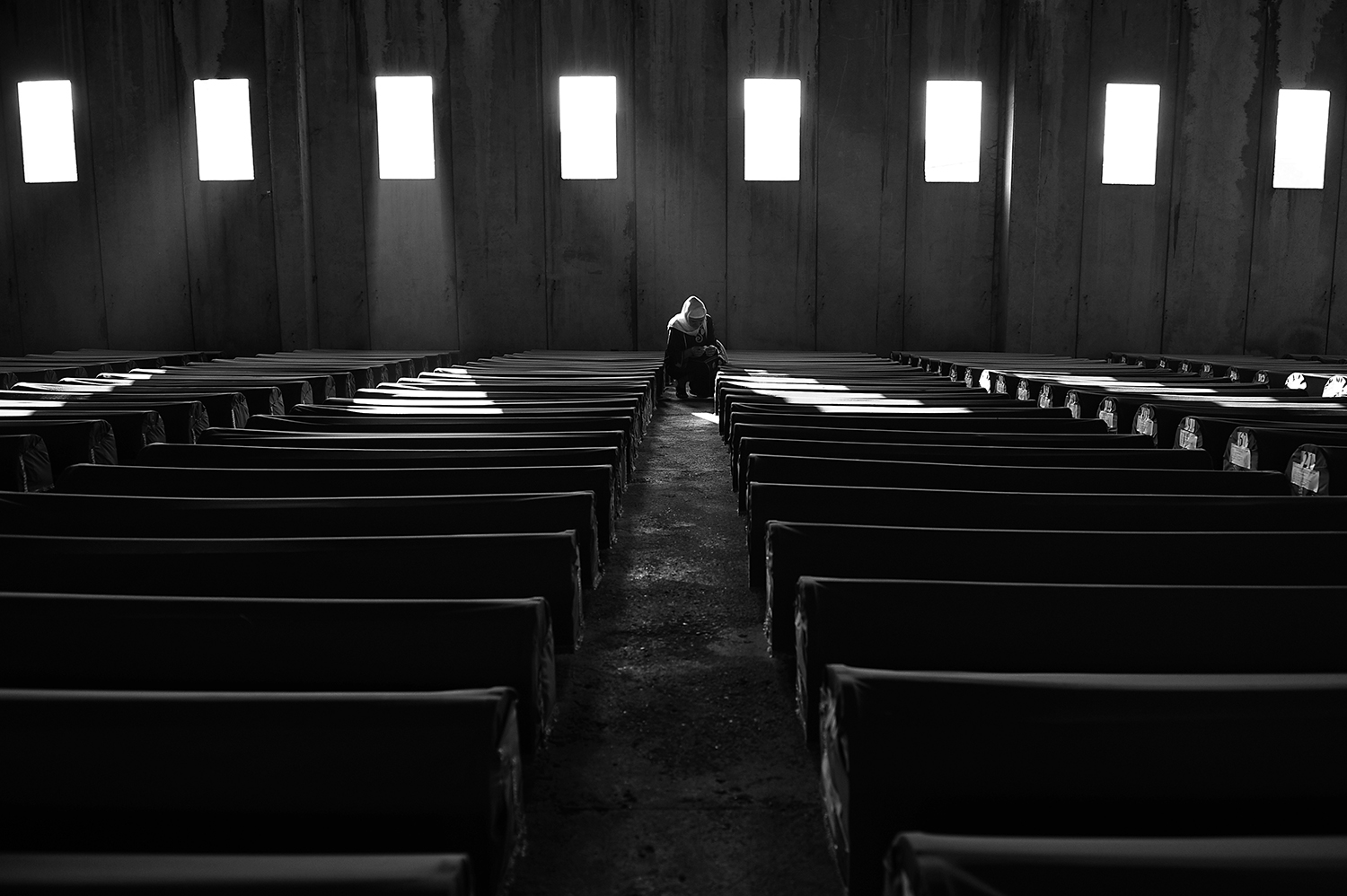 A Bosnian Muslim woman prays near the coffin of a relative, among 520 newly identified Srebrenica victims, which are stored in the abandoned hall of a car battery factory in Potocari near Srebrenica. The bodies were transported from Visoko and stored during preparation for Sunday's funeral of newly identified bodies of Muslims.