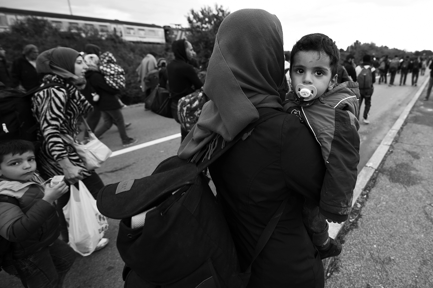 A woman carries a child as she leave the railway station Botovo, near Koprivnica, Croatia. Several thousand refugees arrived by train and started to walk towards the Hungarian border, which will be closed after a few hours.