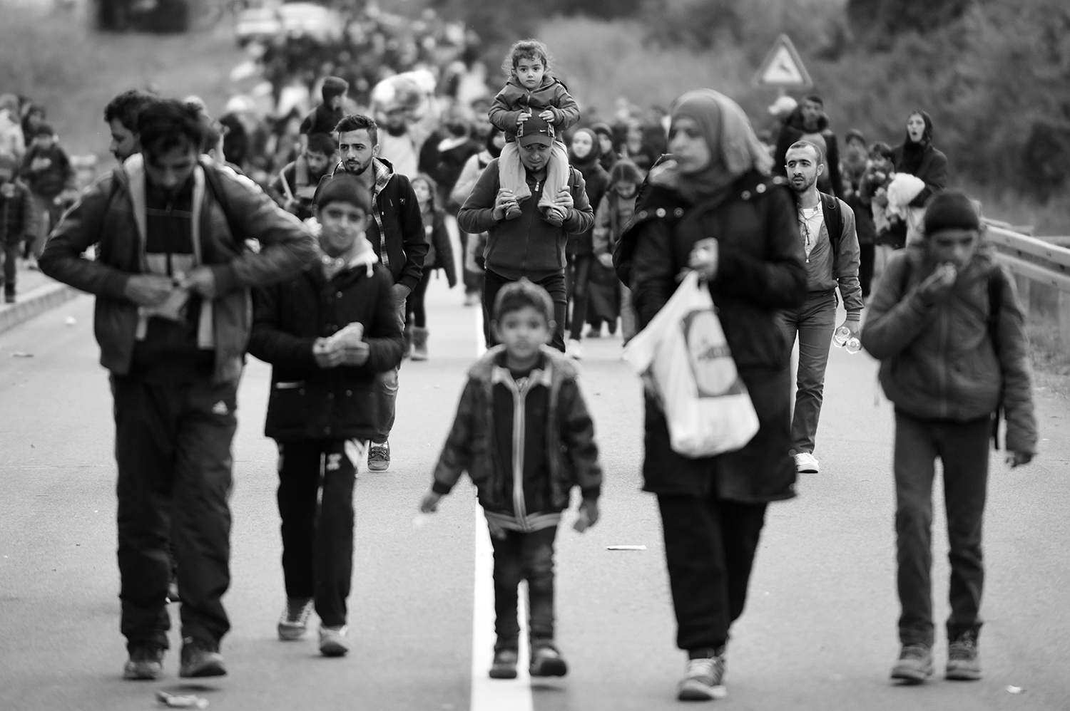 Refugees from the Middle East are walking down the road in a place Botovo, near Koprivnica, Croatia. Several thousand refugees arrived by train and started to walk towards the Hungarian border, which will be closed after a few hours.