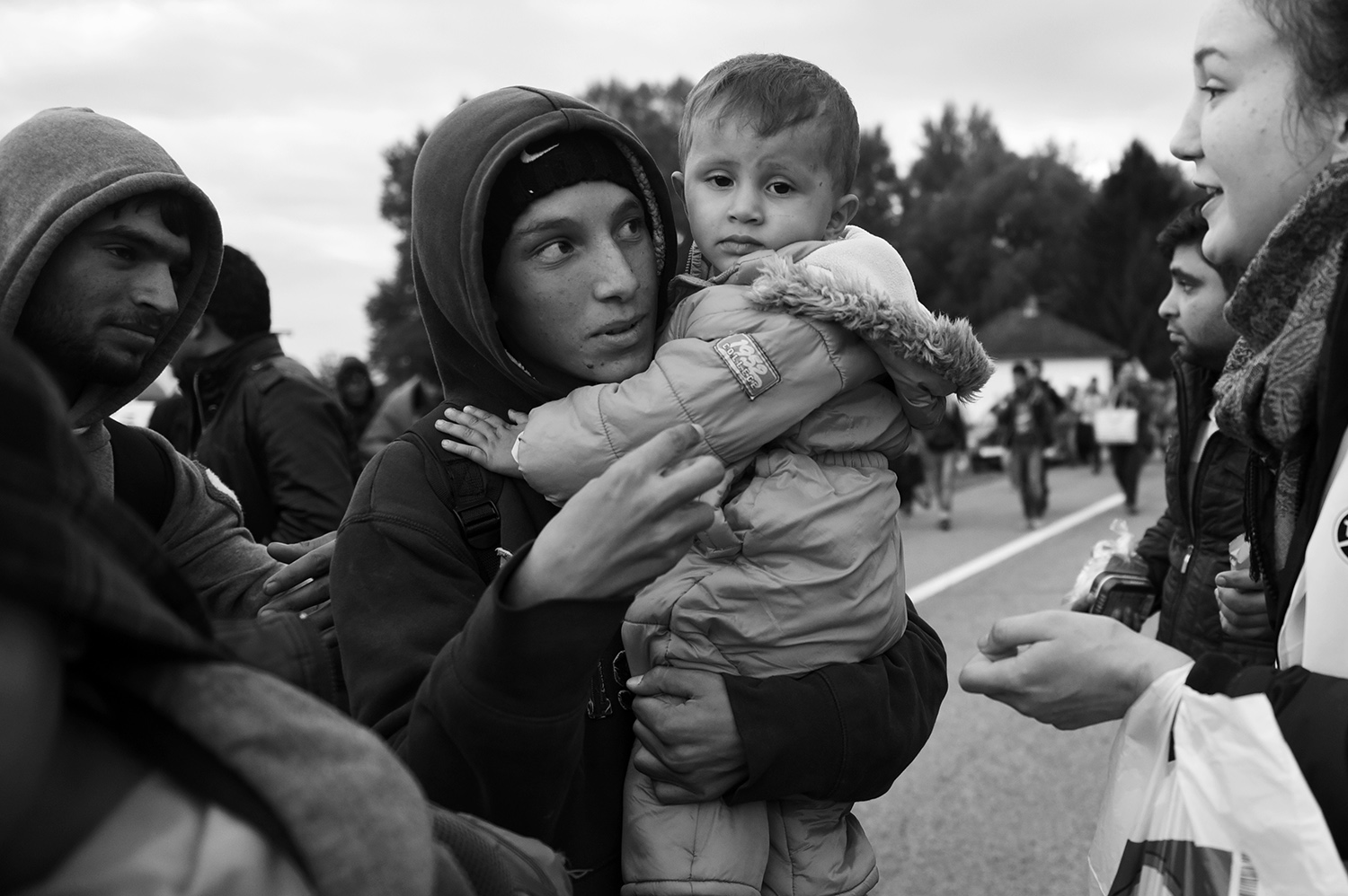The boy holds a child while he talks to volunteers who distribute food and clothing to refugees who arrived in a place Botovo, near Koprivnica, Croatia. Several thousand refugees arrived by train and started to walk towards the Hungarian border, which will be closed after a few hours.