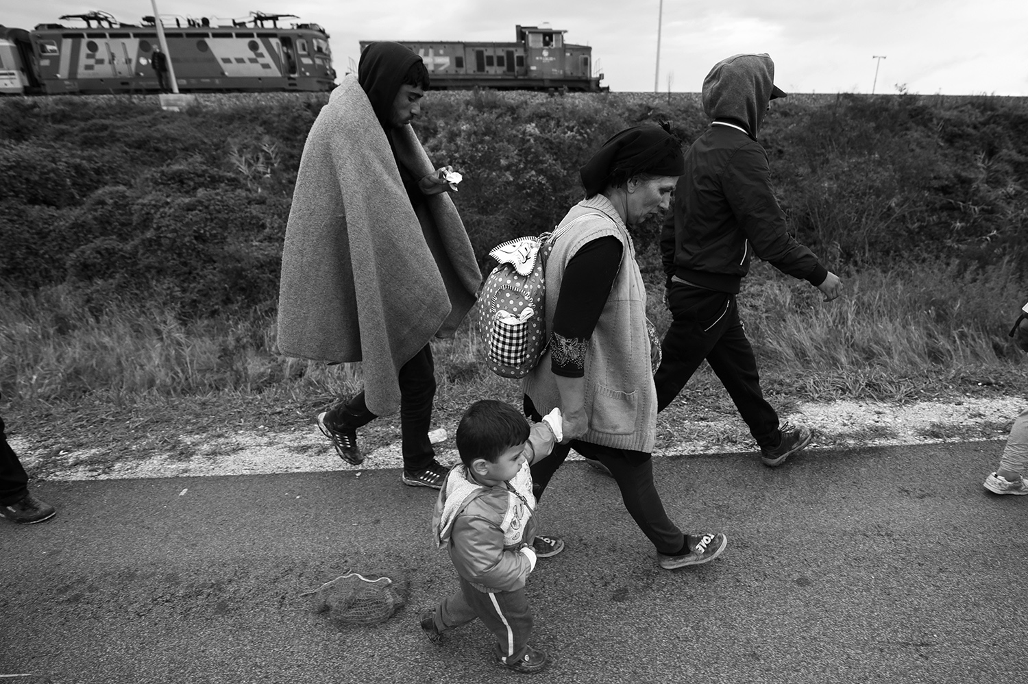A woman walks with a child as she leave the railway station Botovo, near Koprivnica, Croatia. Several thousand refugees arrived by train and started to walk towards the Hungarian border, which will be closed after a few hours.