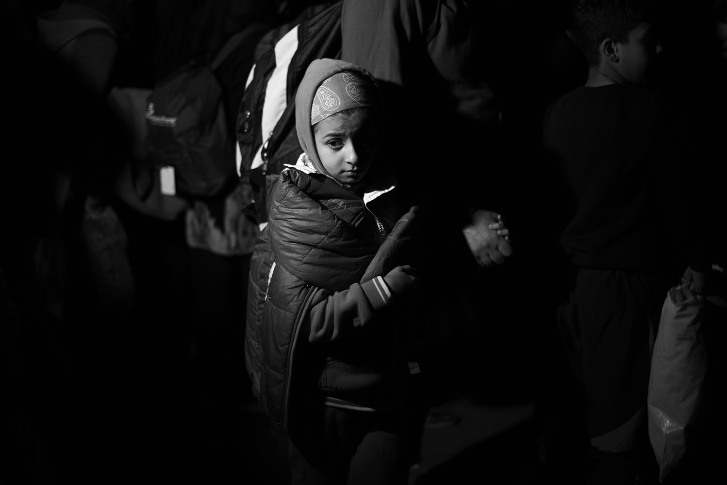 The girl is holding the hand of her parents while she is waiting to cross into Hungary to reach the train which travels to Austria. The night is cold, all refugees want to get on the train because Hungarian border will be closed in a few hours.