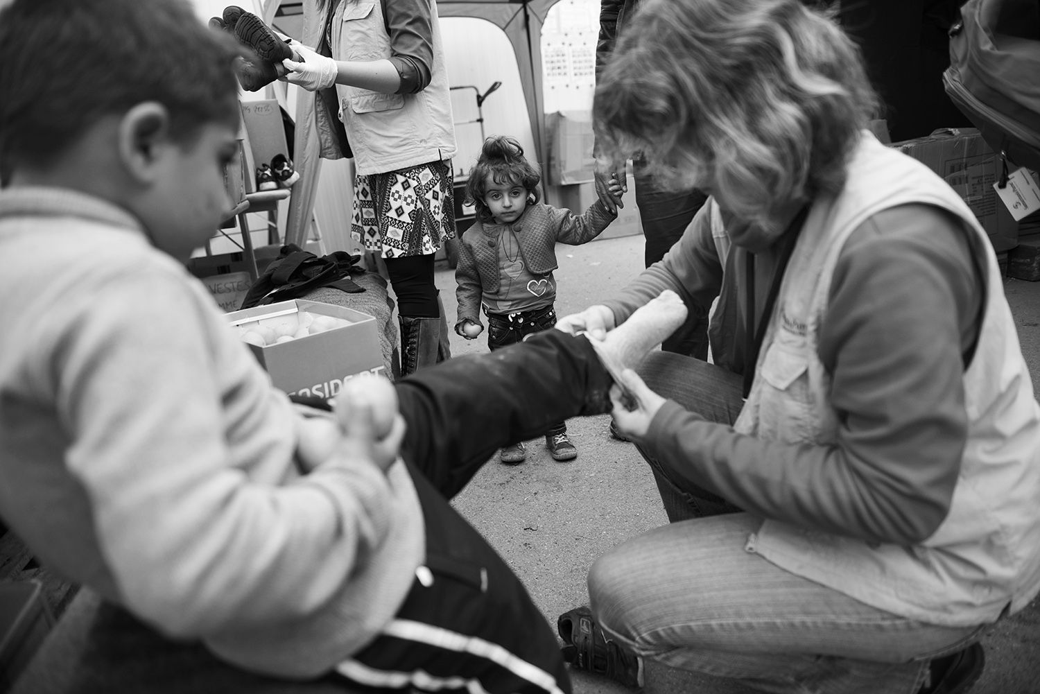 A little girl is standing with her parents while a member of a humanitarian organization puts on socks to her brother at the reception center in Opatovac, near the town of Tovarnik Croatia. Some of the children during the journey were left without shoes and socks, some children is replaced wet shoes for dry shoes. After registering, the refugees continue their way to Slovenia, most refugees want to get to Germany.