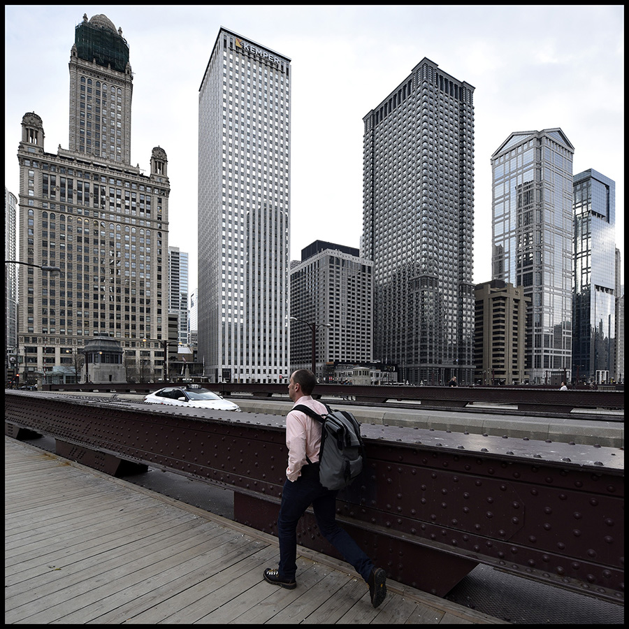 """A man crosses the Irv Kupcinet Bridge in Chicago,Illinois, USA.  In 1930 this bridge received the """"Most Beautiful Steel Bridge"""" award from the American Institute of Steel Construction.Today, there are a number of bridges in Chicago that display the railing height truss design, and they are all attractive structures, however the older examples like this one display more ornate bridge tender houses. There are three railing height trusses, including Wabash Avenue Bridge, that are located one right after another on this section of the river. Of those three, this is the oldest."""
