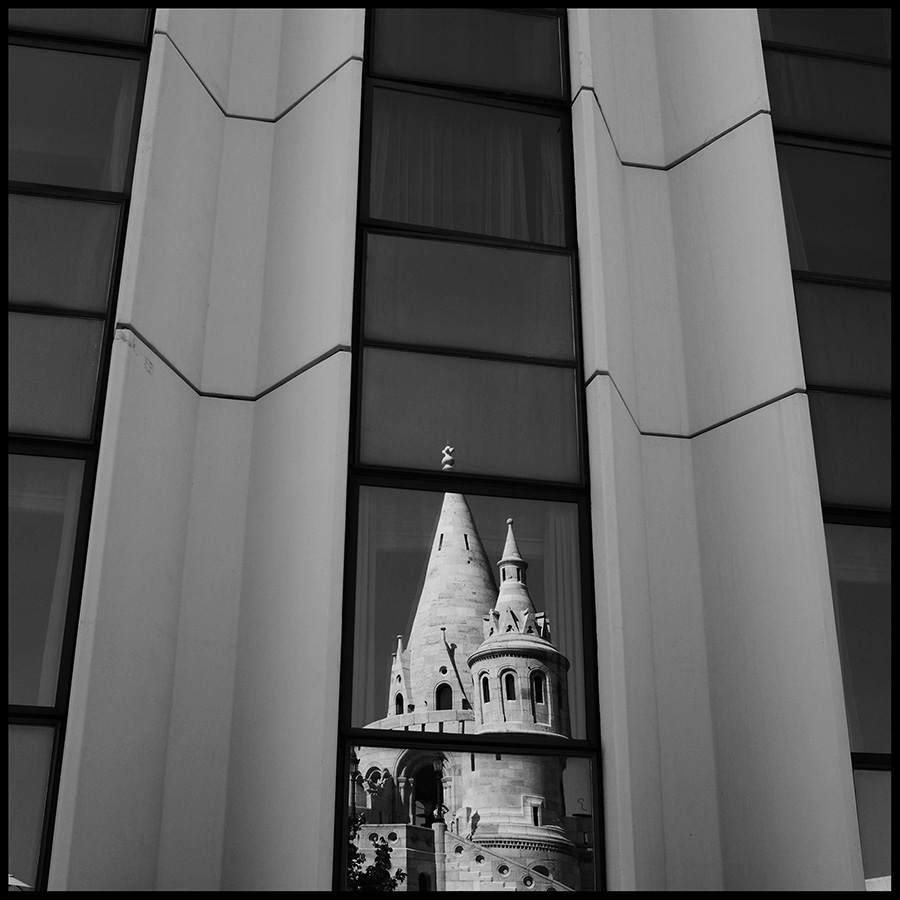 Reflection of Fisherman's Bastion in the windows of the Hilton hotel.Fisherman's Bastion is a terrace in neo-Gothic and neo-Romanesque style situated on the Buda bank of the Danube, on the Castle hill next to Matthias Church.
