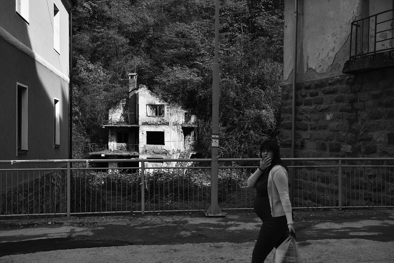 A woman passes by a destroyed house in the center of Srebrenica. The first returnees came back in 2000, but only a few thousand returned in the next few years. The results of the population census in Bosnia and Herzegovina from 2013 showed that in the municipality of Srebrenica live 13.409 residents. of which 7,248 Bosniaks, 6,028 Serbs, 16 Croats.