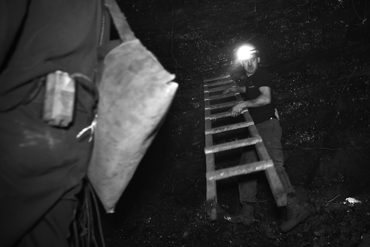 21-year-old Emir Kalota sets ladders to help the coal miner drill holes high on the wall of the coal mine.