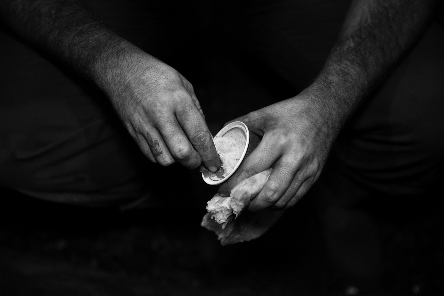 Dusty hands of coal miner who eats his meal during the break.The only thing next to their equipment they may carry in the coal mine is a bottle of water and lunch.