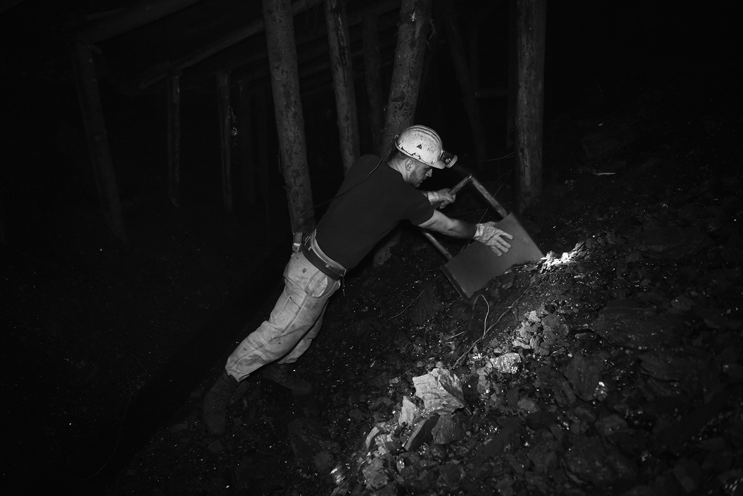 Adil Muhic, using a shovel, pushes the coal on a conveyor belt that draws coal to the surface.