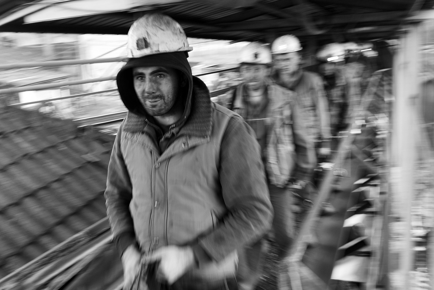 Coal miners on the conveyor belt comes out of pit which transports the coal to the surface.