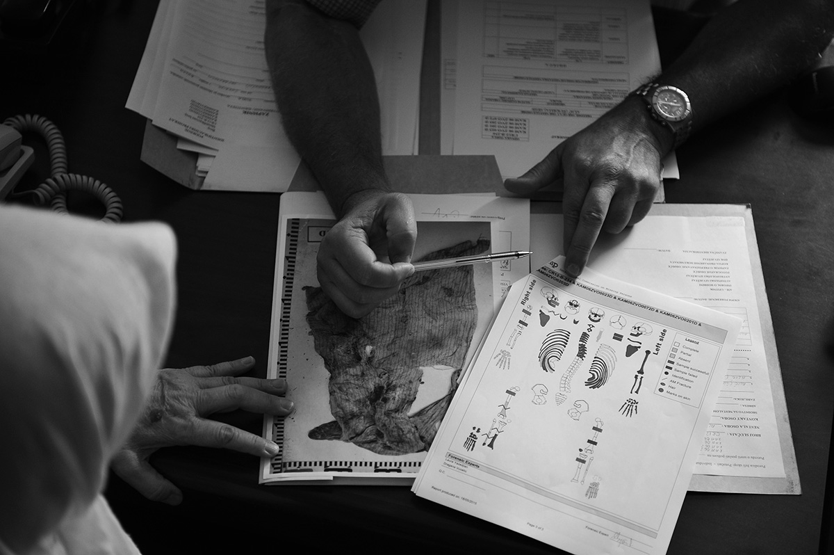 ICMP staff present Mother of Srebrenica Dulsa Alic with a diagram of uncovered skeletal remains and photos of clothes found in a mass grave, so that she can help finalize the process of identification of her son. Tuzla, Bosnia and Herzegovina.