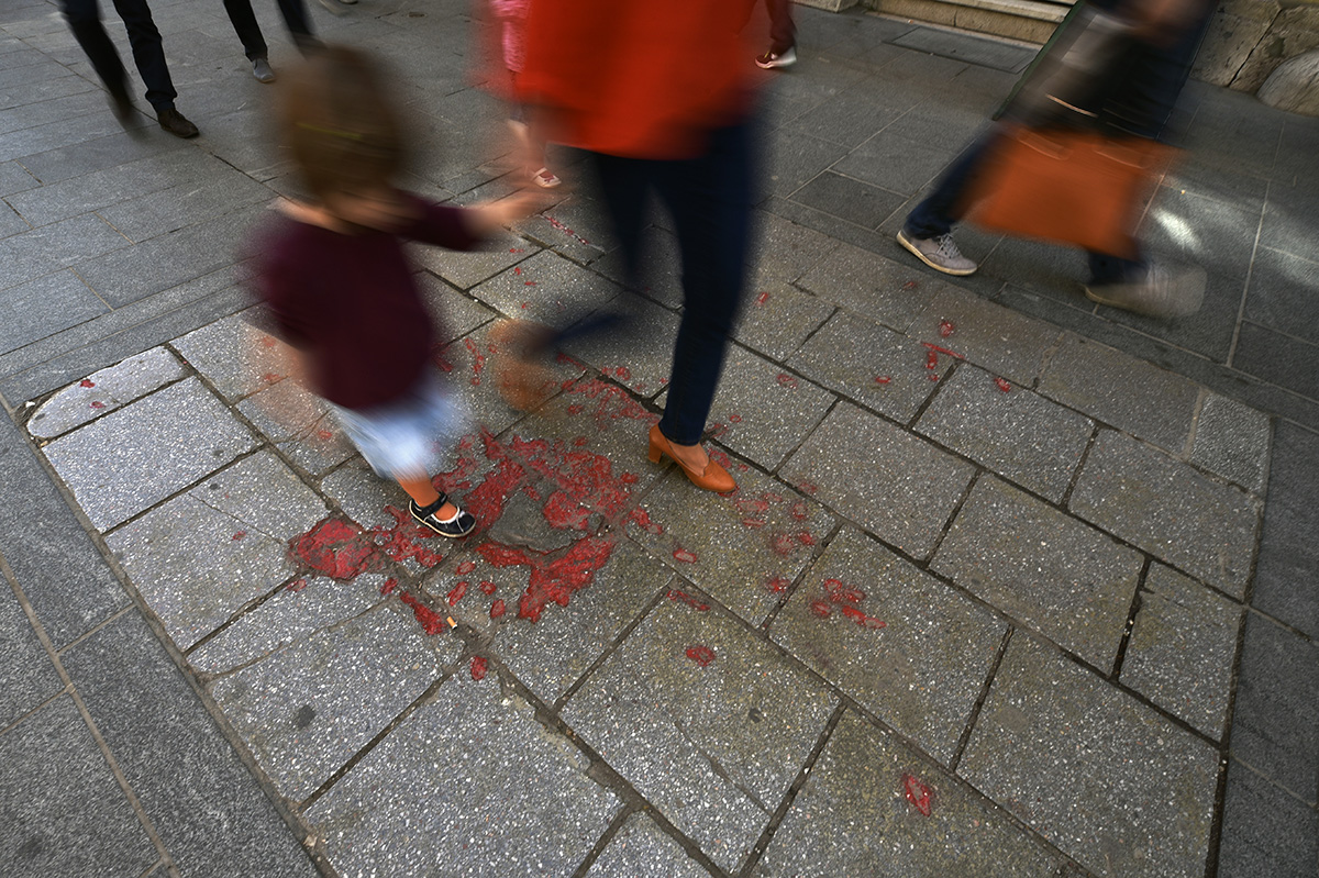 """People passing by a """"Sarajevo Rose"""" in the BiH capital city. Throughout Sarajevo, concrete scars caused by mortar shell explosions have been filled with red resin as a memorial to those who lost their lives during the Siege of Sarajevo. Lasting 1,425 days, this was the longest siege of a capital city in the history of modern warfare. Bosnia and Herzegovina"""