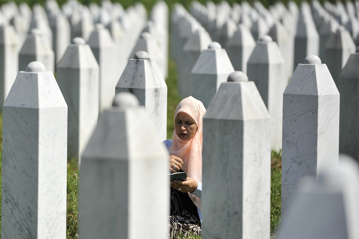 A woman prays at the grave of a loved one in the Srebrenica-Potocari Memorial Center and Cemetery. To date, 6,377 people have been buried here. Bosnia and Herzegovina
