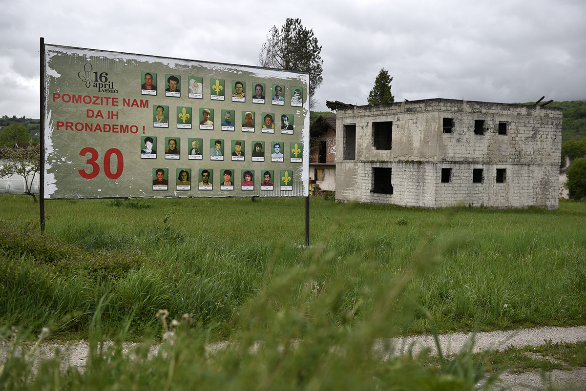 "A destroyed house and a billboard sit on opposite sides of a line of demarcation between Bosnian Croats and Bosnian Muslims. The billboard reads: ""Help us find them"". It contains the names of Bosnian Muslims massacred in 1993 by HVO forces (the main military unit of Croats of Bosnia and Herzegovina) in the nearby village. Ahmici in central Bosnia and Herzegovina."