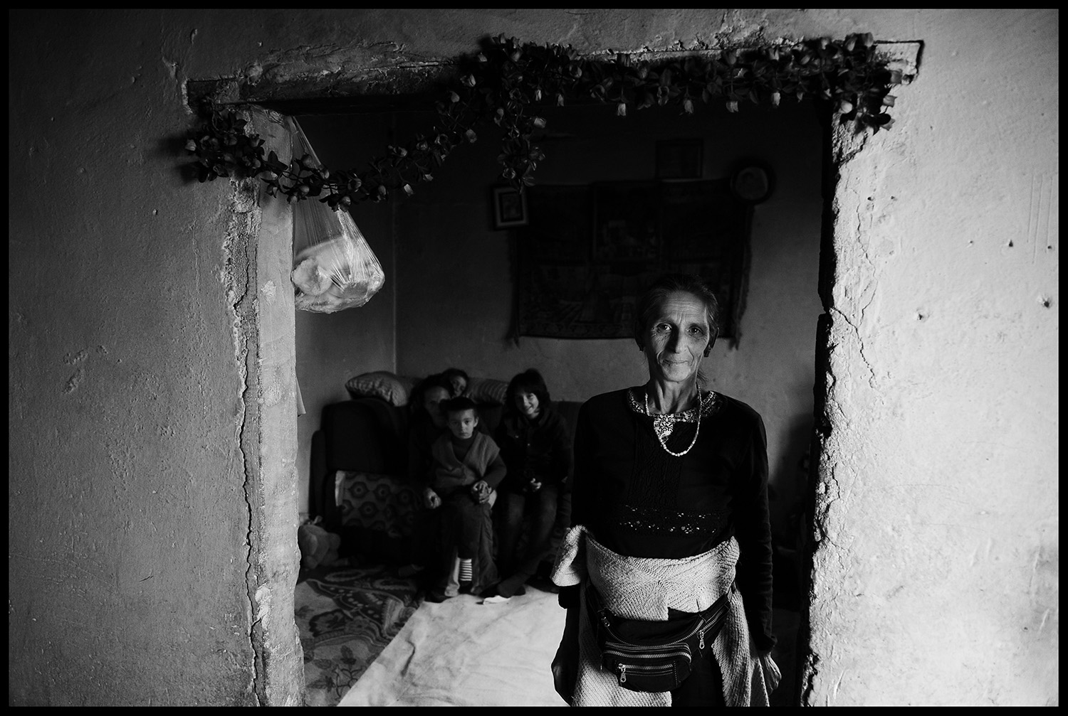 "The mother of twelve children Refija Zahirovic stands at the entrance of twelve square meters room, which is actually their home in Visoko, Bosnia and Herzegovina. Without bathroom and basic living conditions, she tries to motivate her children to continue their education. Of the twelve children, only one so far has completed elementary school. Mother Refija is determined that the younger, four of them, have at least eight grades of elementary school. According to official data, Roma are almost 100% unemployed. Whether a Roma child attends school largely dependent on parents, because some, thanks to education, manage to get out of the ""vicious circle of poverty"", while others remain on the margins without any financial or health security."