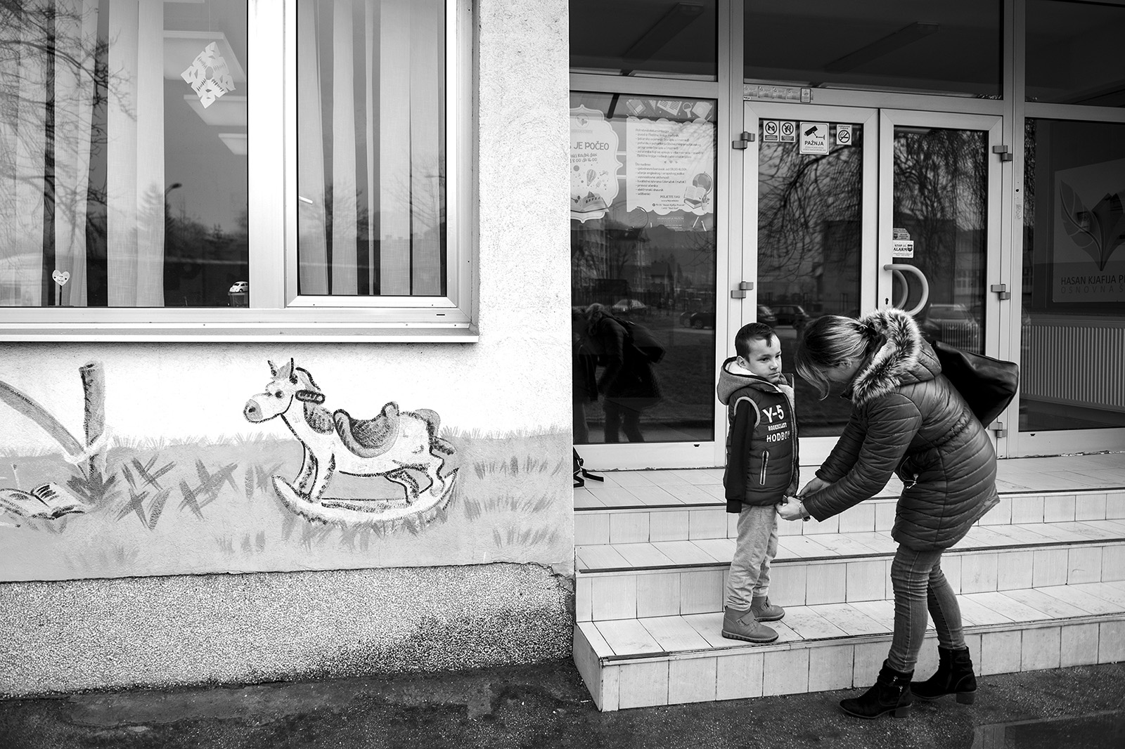Elmina and Ismail after the school day in front of the elementary school Hasan Kjafija Pruscak in Zenica.