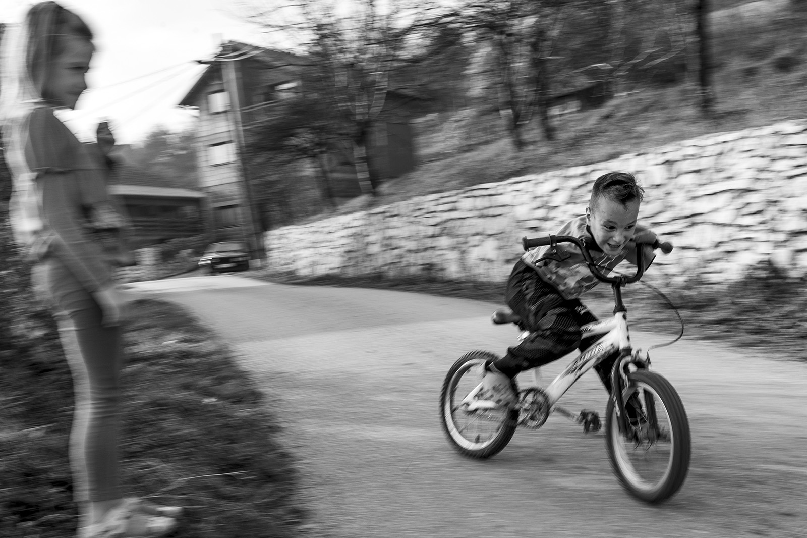 Ismail shows his sister how to drift on a bicycle on the road next to their house in Zenica.