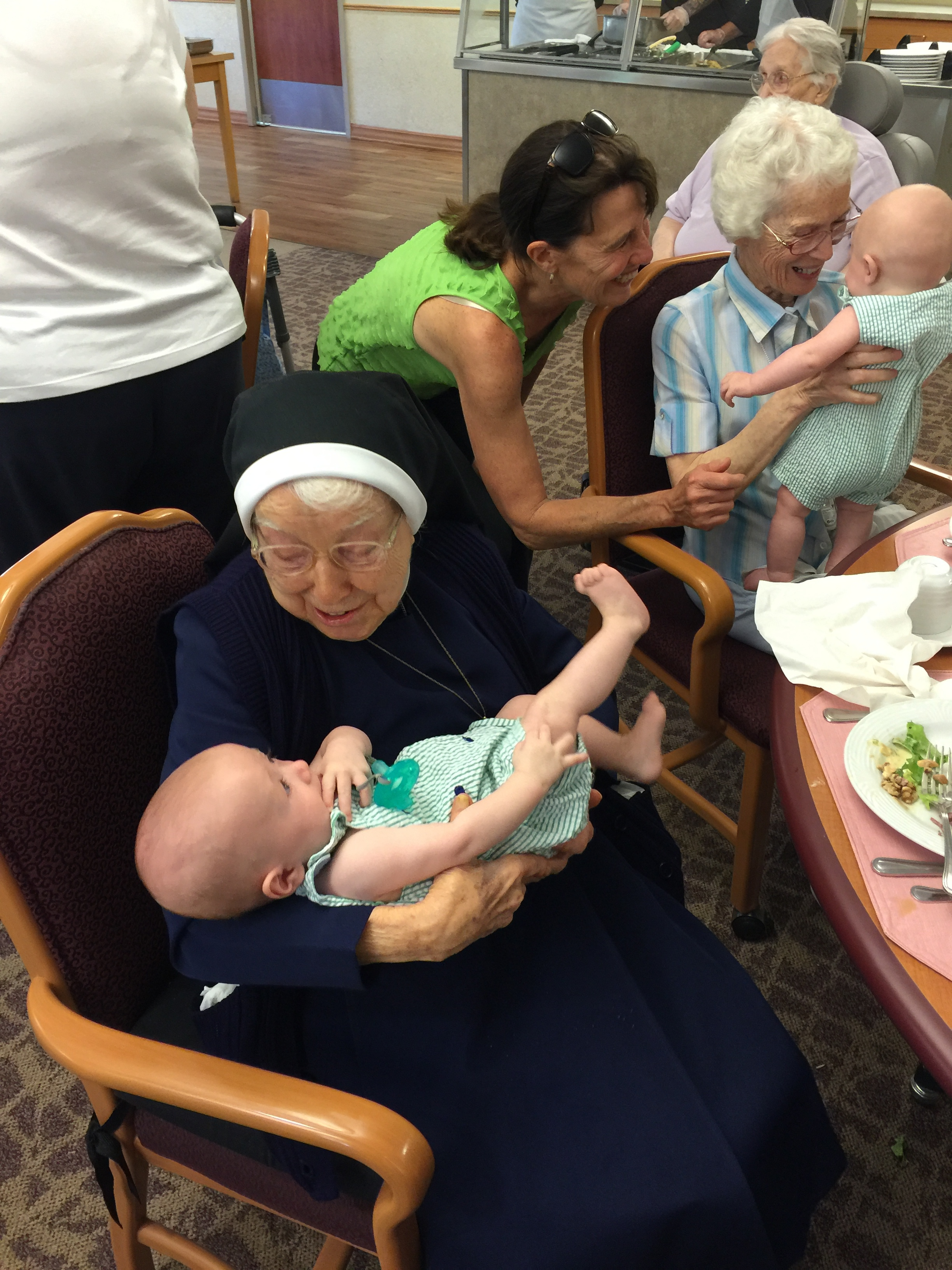 """This is Sister Romaine Krug holding baby Charlie - she is 102 years old, the 3rd of 15 children and was a """"baby nurse"""" prior to being a nun. She said in all of her years working with babies she had never met quadruplets. She also called Charlie a pistol...spot on!"""