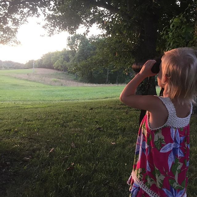 Claire's first time using binoculars. She was amazed to be able to see the evening deer up close.