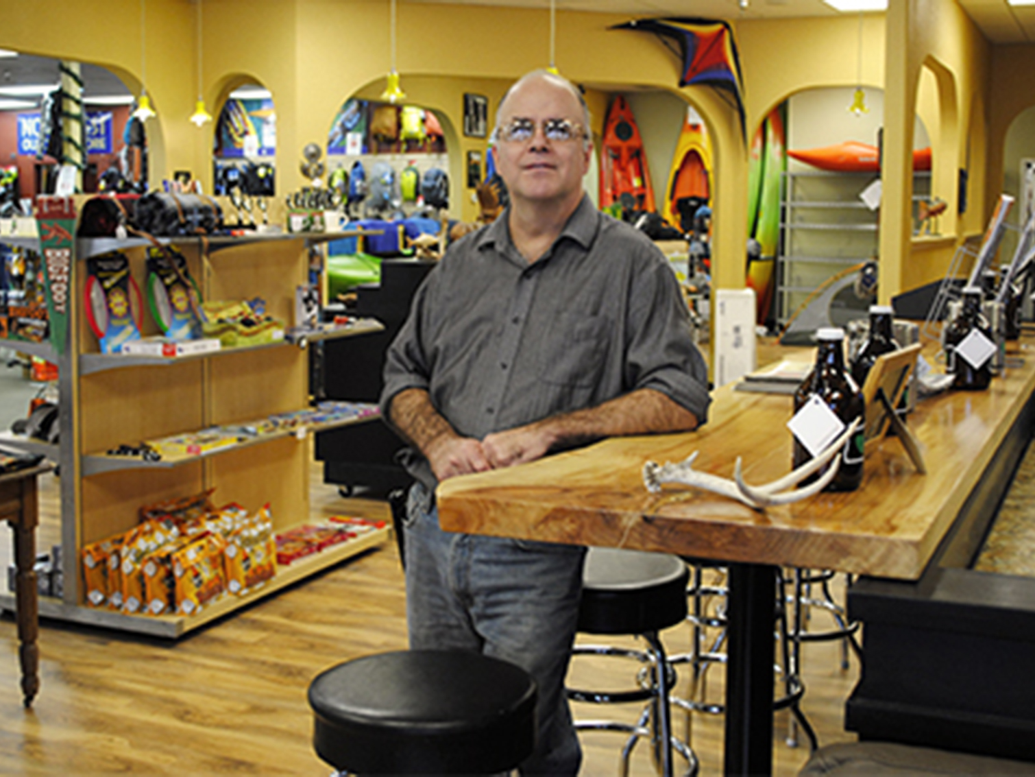 Northwest Outdoor Store owner, Scott Keith next to his new bar top.
