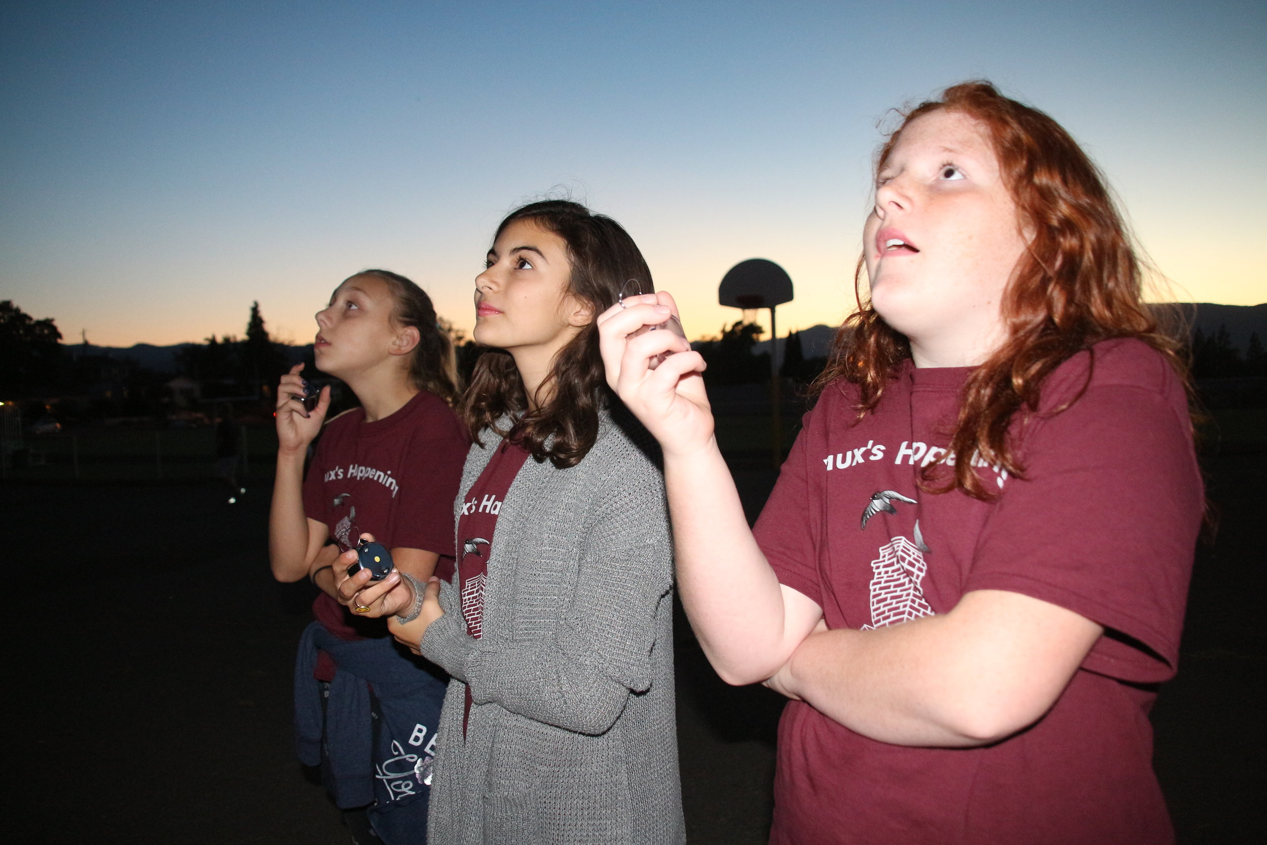 Three 7th grade Hedrick Middle School citizen scientists grip their tally counters with eyes glued to the school's chimney. They are poised to count the swifts entering their evening roost during fall migration as part of the citizen science program called  Vaux's Happening .