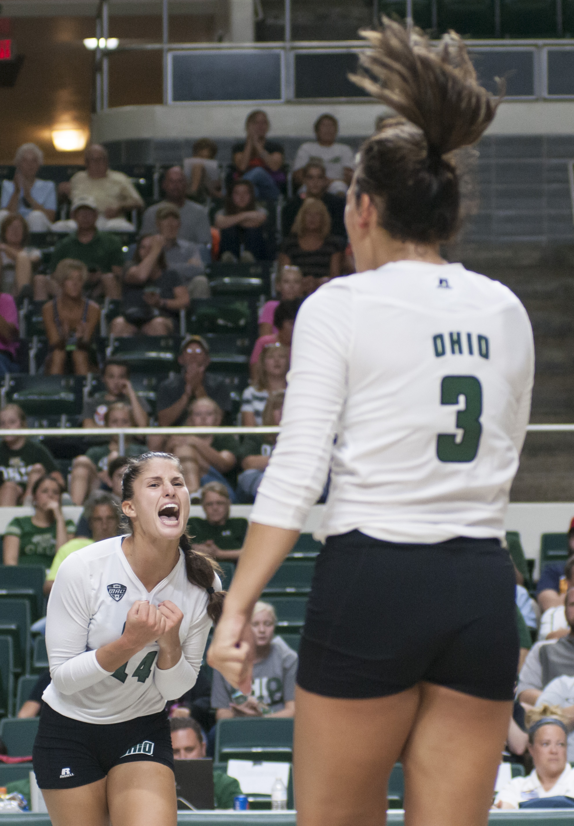 Ohio University's Jaime Kosiorek and Abbey Gilleland celebrate a point made against University of Michigan on Saturday Sept. 5, 2015 in the Convocation Center in Athens, Ohio.