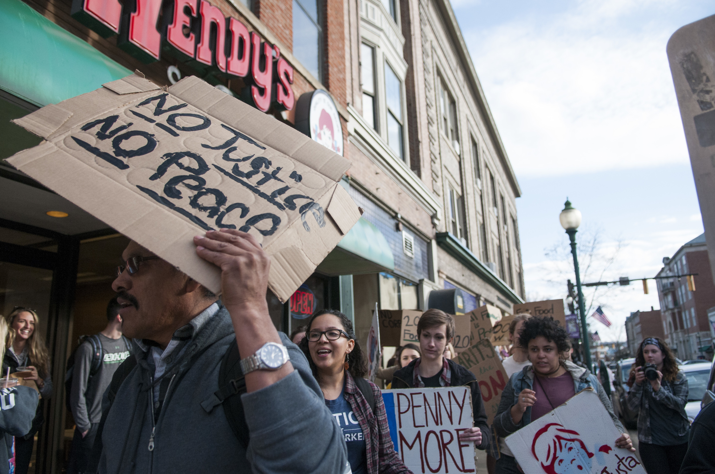 Santiago Perez, a representative from the Coalition of Immokalee Workers, holds up a sign while he walks into the Athens, Ohio Wendy's on Tuesday, Feb. 23, 2016. The protesters worked with the coalition to ask Wendy's to pay one more cent for tomatoes to help pay farm workers higher wages.