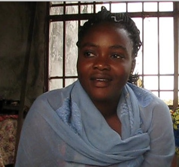 "Makongolo Dina - ""I am called Makongolo Dina. I am 3rd of 6; our father died when we were young. We did not go to school, except my oldest brother who paid his own way. One of my sisters told me that there was a non-profit here where you could study sewing. I wanted to do that; I came and talked with Mme Monique and she accepted me. When I came I could not read or write but now I have learned to read and write and I am learning to sew. There were many things I did not know but now I am learning and advancing. I am not married but I have two children, a boy of six (in first grade) and a girl of eight (in third). I had lots of problems; there were times when I did not have anything to eat for three days, and nothing to wear. That is how I got acquainted with a policeman. Policemen are not well paid; he gets $40 or $50 a month. So he does not have enough money to rent a house for his family, but he supports his children. Every few days he brings about 3000 or 4000 Congo francs (less than $5) to buy food for the children. Sometimes he gives me 10,000 francs to buy them clothes. When he gets his salary he pays their school fees. I like to sew because in the future that will allow me to support myself. If I have my work, I will not wander here and there, or prostitute myself to have a little money. I will be able to take charge of my life myself."""
