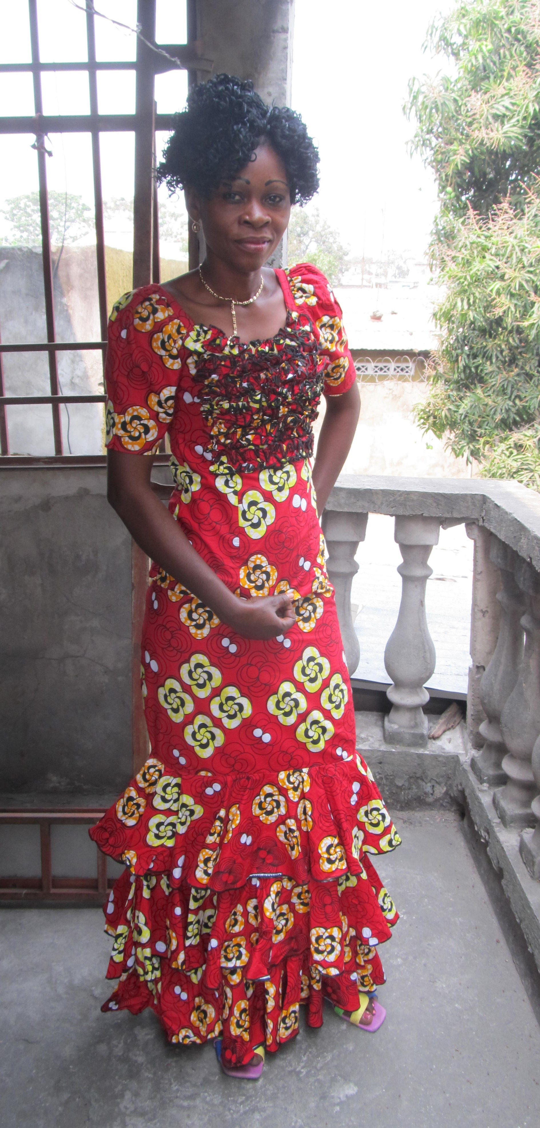 "Jeannette Boyata - ""My name is Boyata Jeannette. I am the wife of a soldier and we live in Camp Kabila. I am very happy to sew. When my husband was passing by FEBA he saw the poster which said they were seeking people who wanted to learn to sew. He talked with me about it, saying, ""You like to sew; I like for you to do it. You are the mother of three children (whom we must educate)."" It was my husband who urged me to come. I enrolled in 2013 and now I sew very well. When someone sees how I sew, he asks where I learned and I say, ""At Mme Monique's."" Also I have brought many young girls to this sewing school.Since the salary of a soldier is not much, I thank God that I can now sew and contribute to our household. I have a sewing machine at my house and I can earn $20 and pay the school fees for my children. The oldest is in the fifth year of secondary, the second is in primary six, and the youngest in primary four. I don't have enough money to open an atelier (shop) for myself. But in spite of that, now we do not lack food. For example, if someone comes with a broken zipper, I can repair it, or if the pants are too big, I can adjust them. That way we can eat. I thank the Lord for this machine. My husband came the day of graduation and saw me in my beautiful dress. He was very happy when he saw the machine (my graduation present from Woman Cradle of Abundance, Inc.). He said, ""Having a machine was a dream and now the dream has come true!"" A machine is something extraordinary in the house. I appreciate Mme Monique very much and I am happy that she invited me here to speak about my life. Many thanks to Mme Monique because she has done so much for us."""