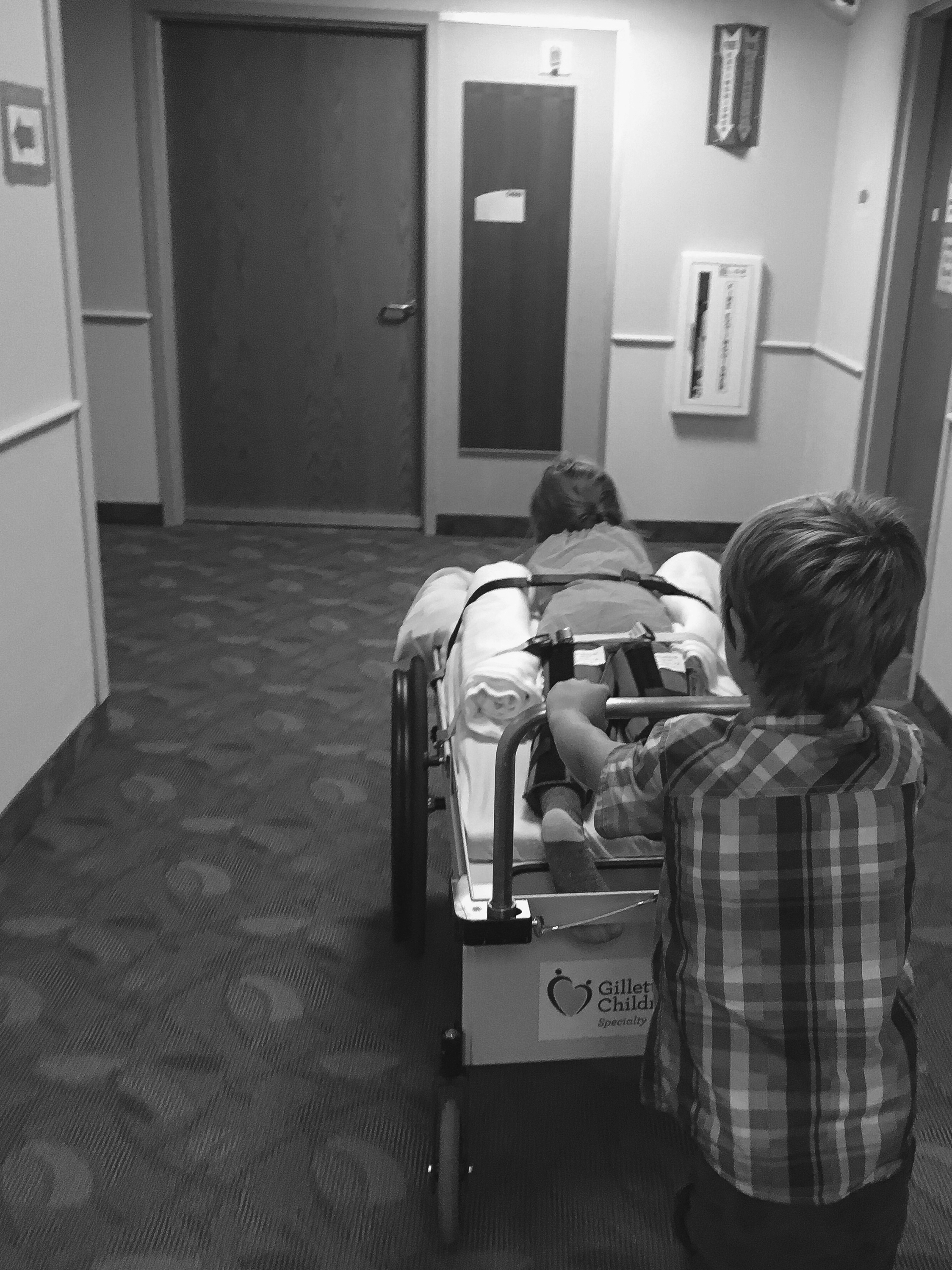 Eli pushing sweet Macie around the hospital for therapy sessions! {took this one on my iPhone!}