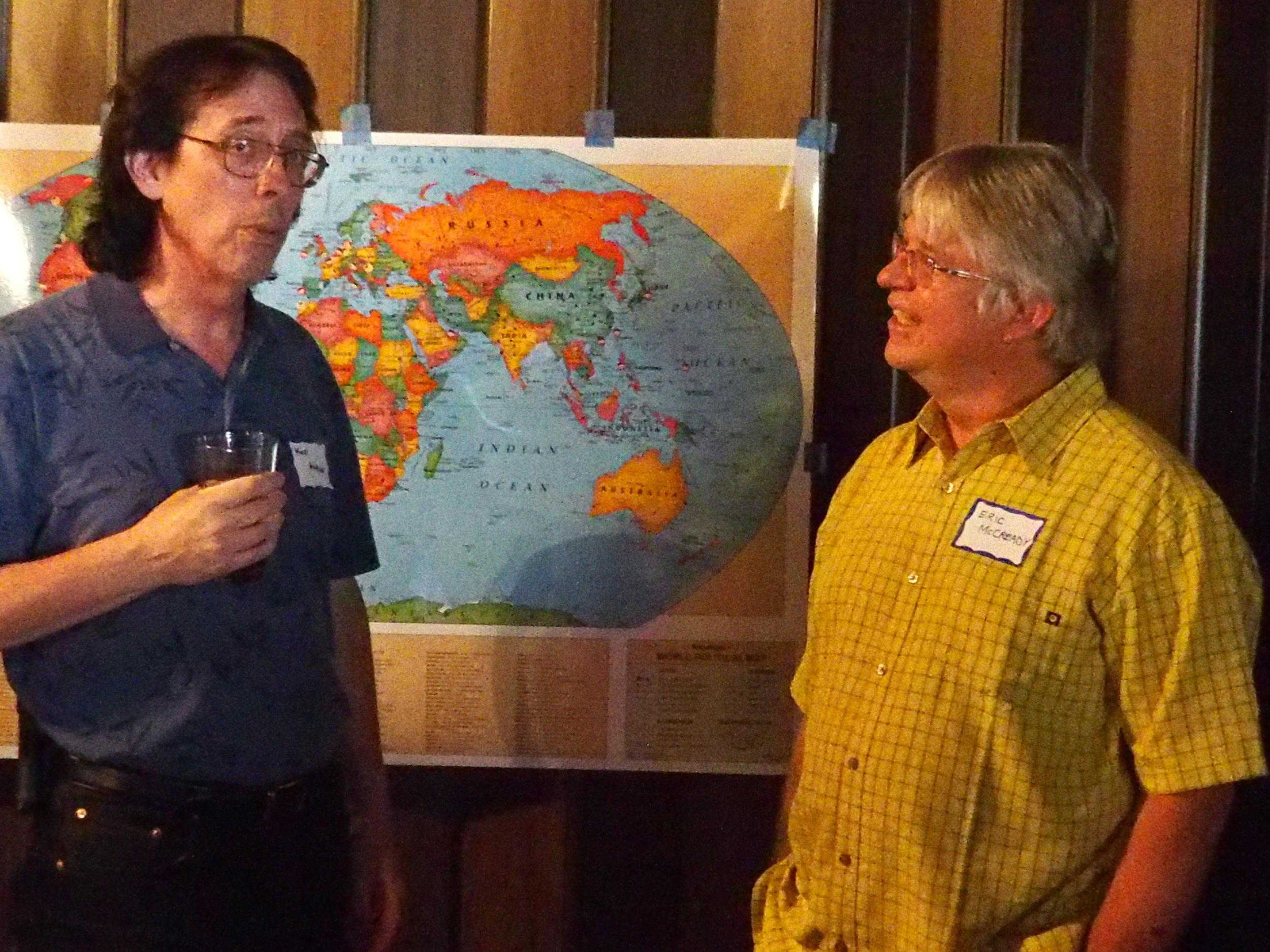 Ken Althiser and Eric McCready in front of the world map.