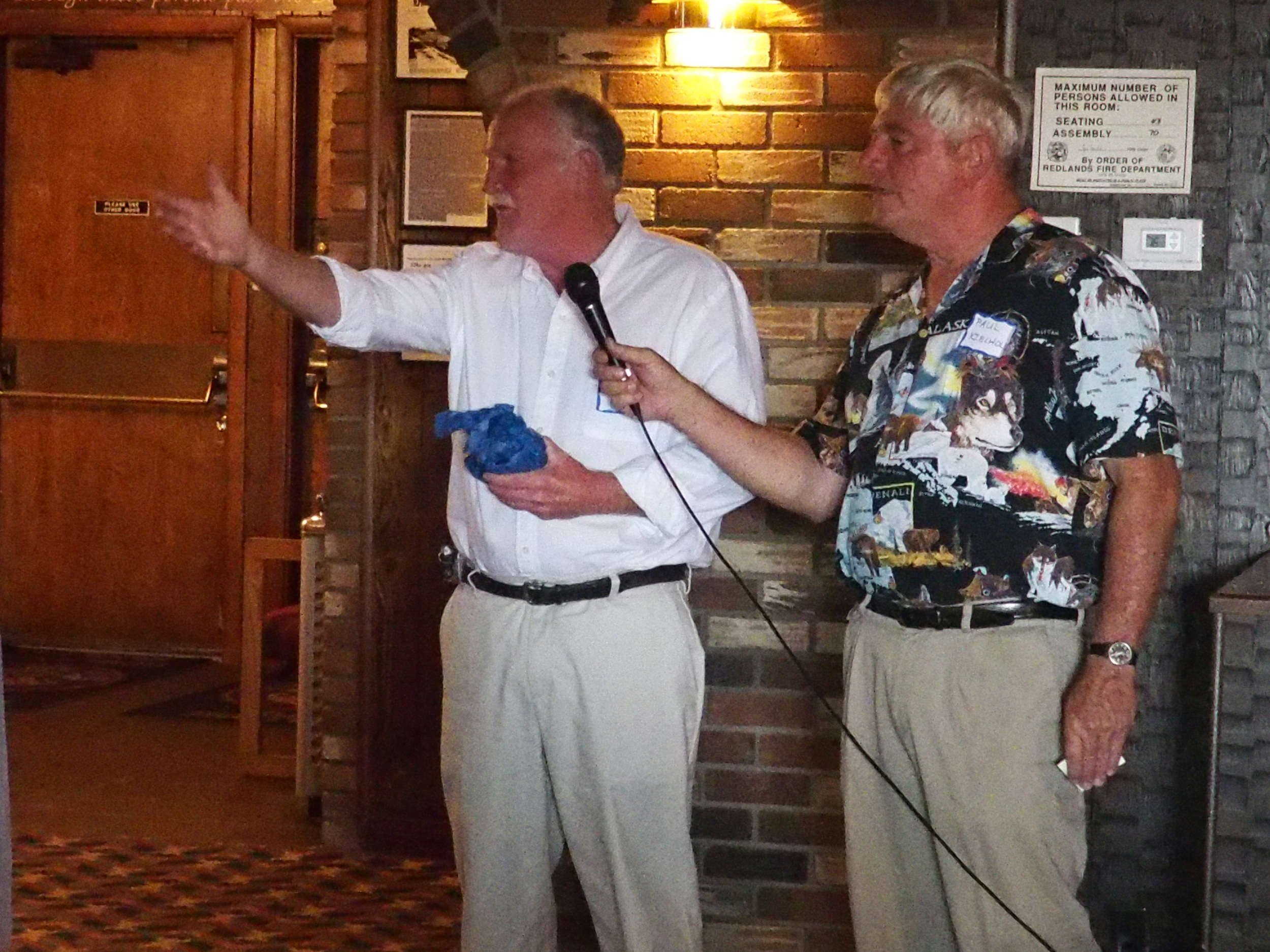 John McKay (with emcee Paul Kielhold) being acknowledged for traveling the farthest