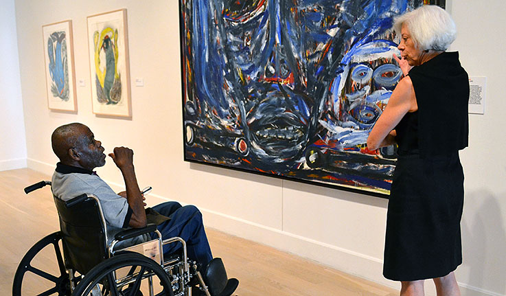 Willie Young view an installation of Thornton Dial's  The Reservoir  (1990) with Weatherspoon Museum Director Nancy Doll last summer.