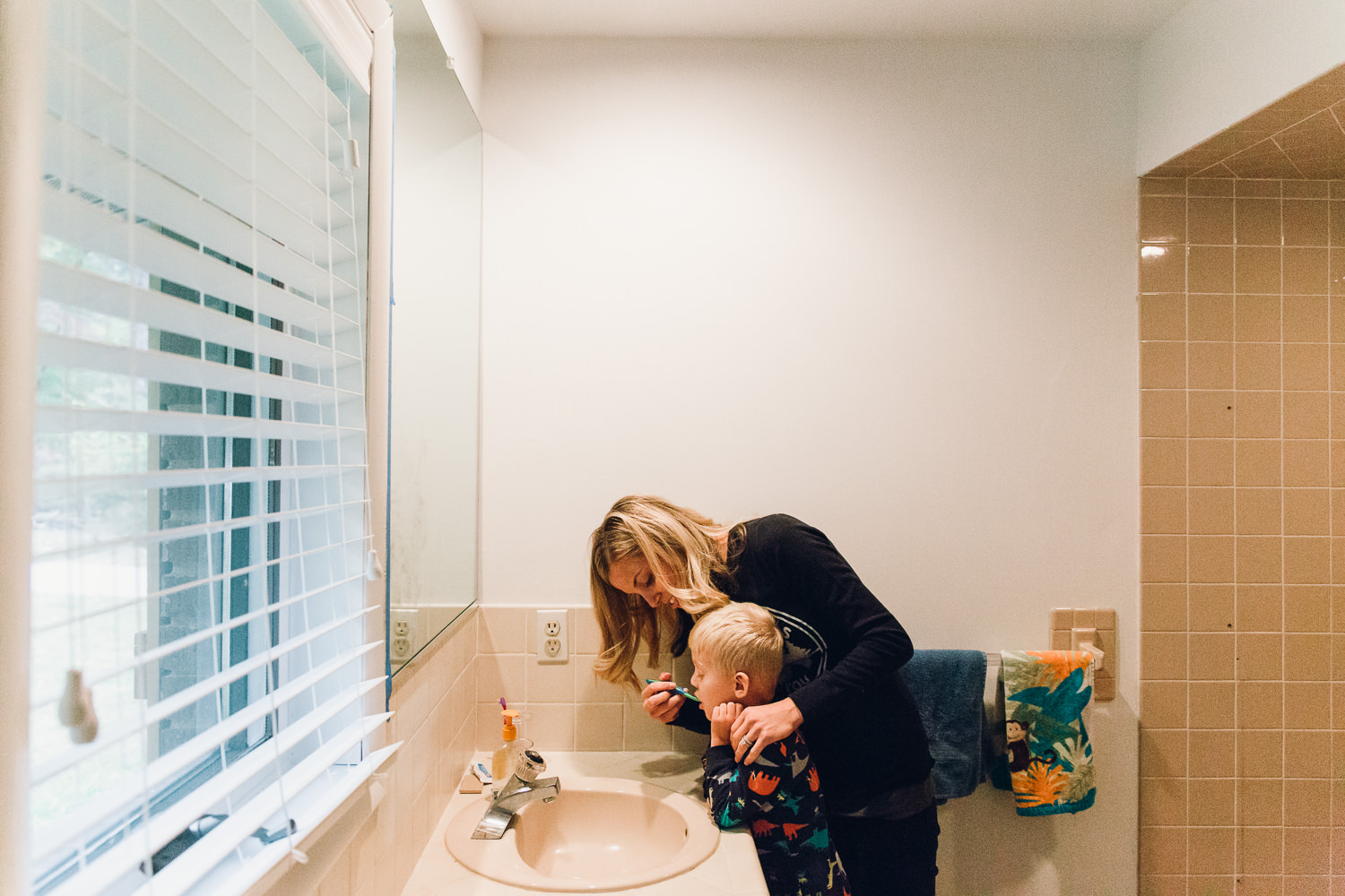 Mom brushing childs teeth during family photos session