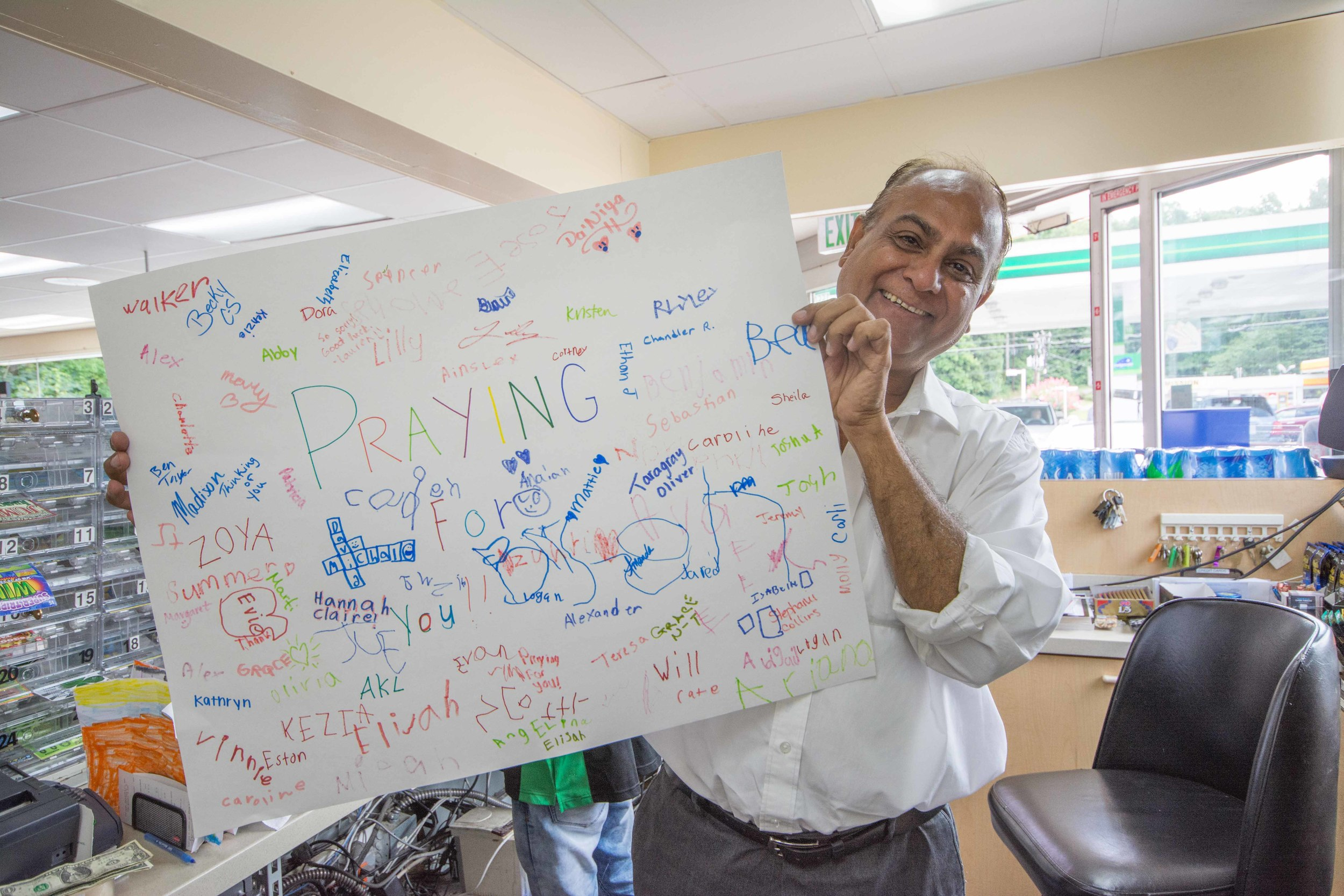 Store owner Bahadurali Waliyani with a card made by Smoke Rise Vacation Bible School children.