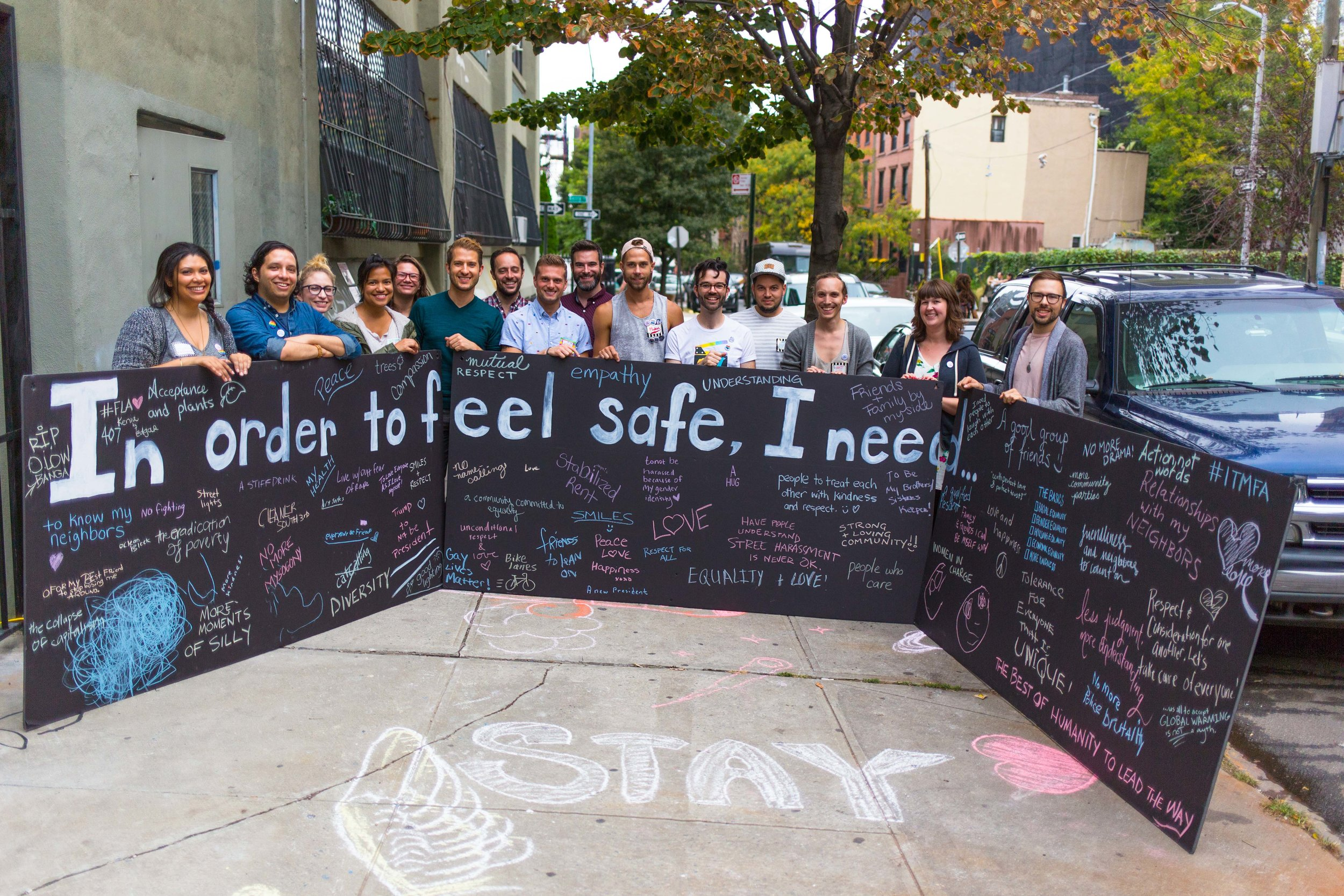 VideoOut staff and volunteers holding one of the Kindness Party activities, an installation inspired by Candy Chang, called In Order To Feel Safe Wall.  Photo by Eric Jenkins-Sahlin / www.EricJenkinsSahlin.com