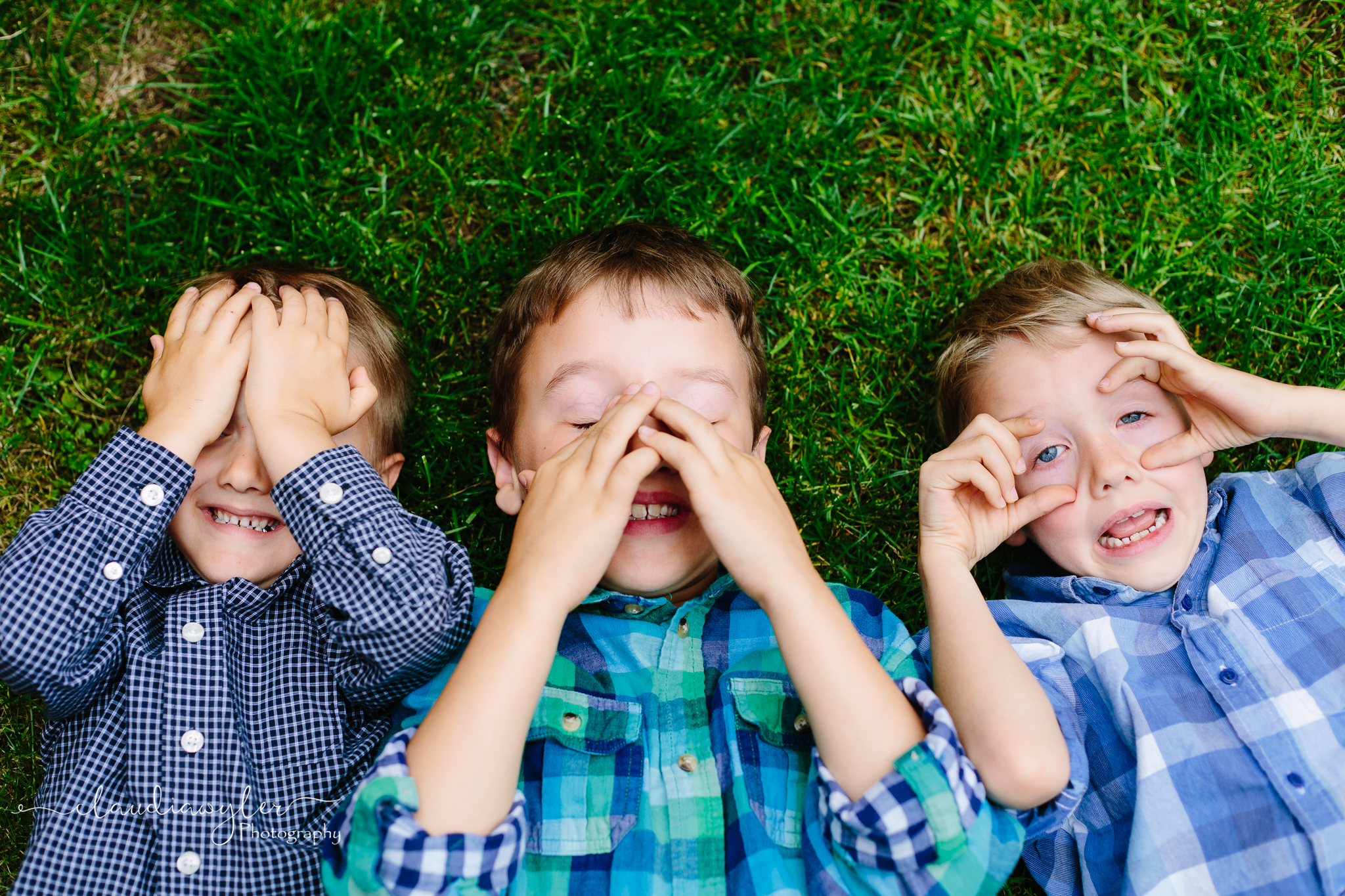 3 young boys playing in grass hidingn faces