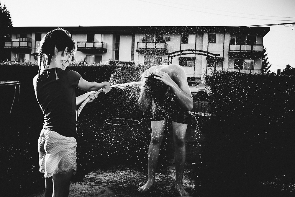 Siblings having water fight with garden house.