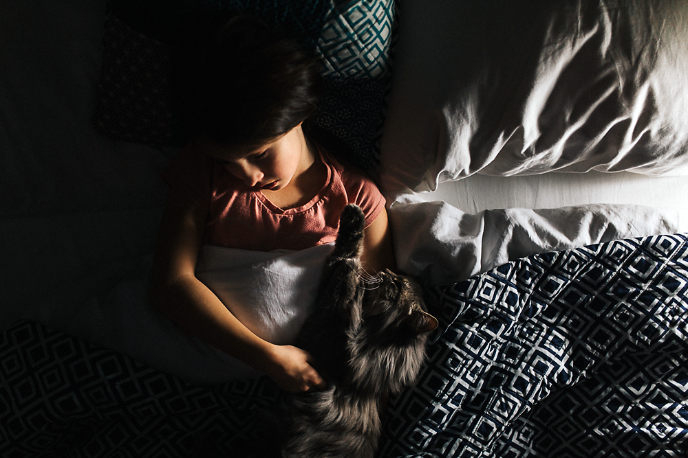 Young girl reading in bed with her cat during family documentary session in Chilliwack, BC