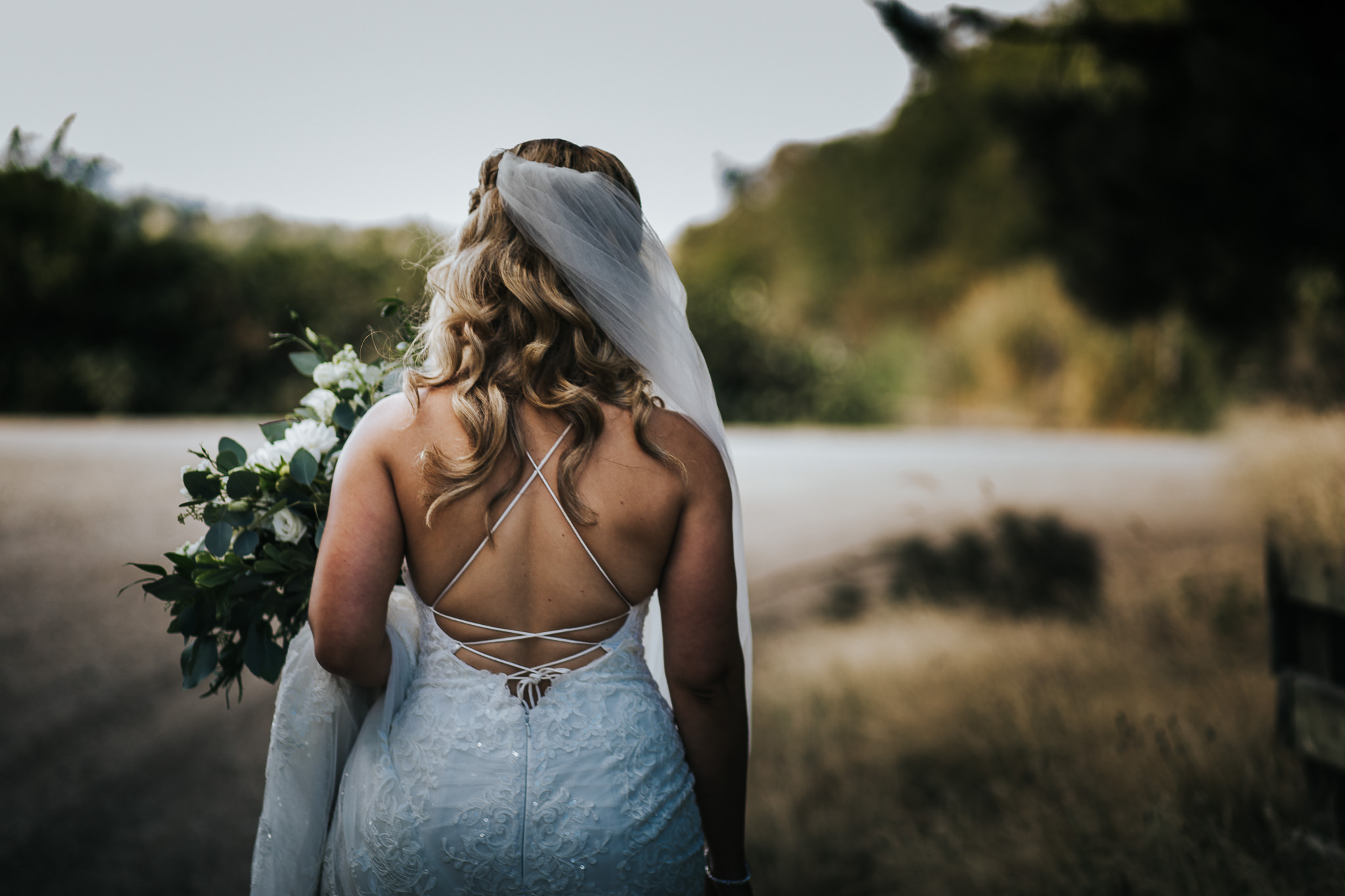 Bride walking through tall grass with road in the distance at sunset at Hazelmere Golf and Tennis Club in Surrey, BC