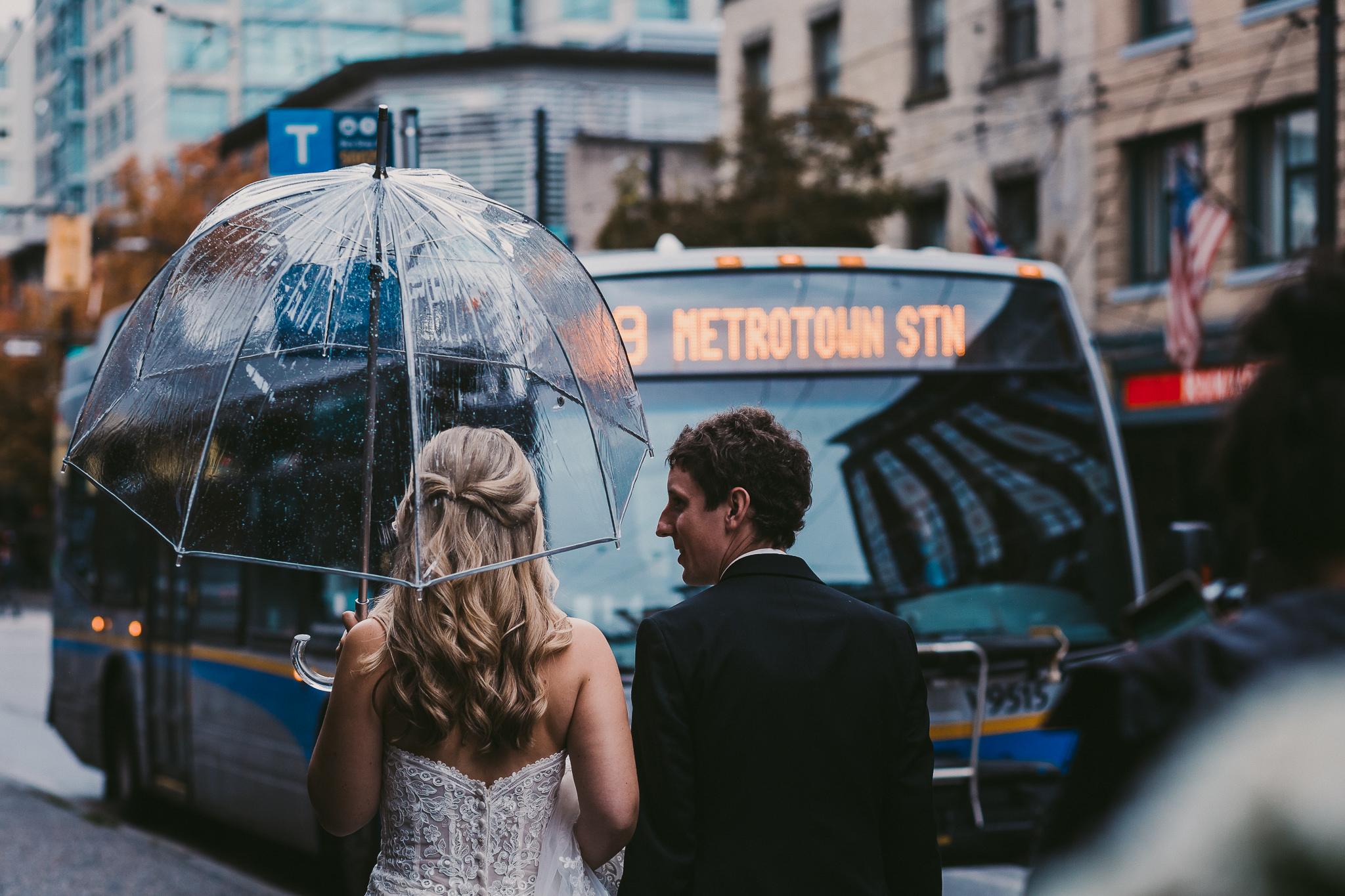 Bride and Groom walking down busy city street in Vancouver, BC in the rain on their way to their wedding. Bride holding umbrella as city bus is driving by.